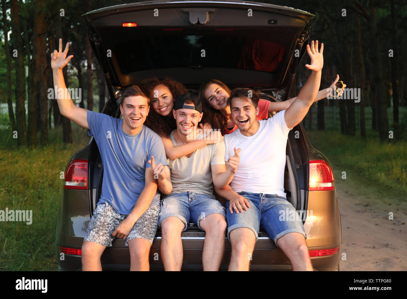 Friends sitting in a car trunk - Stock Image