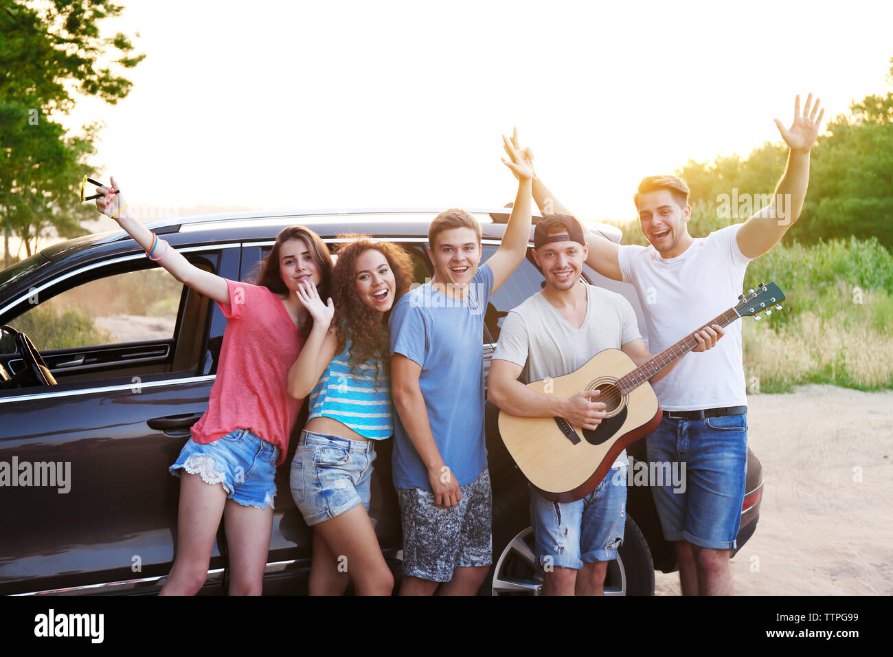 Cheerful friends with guitar near car, outdoors - Stock Image