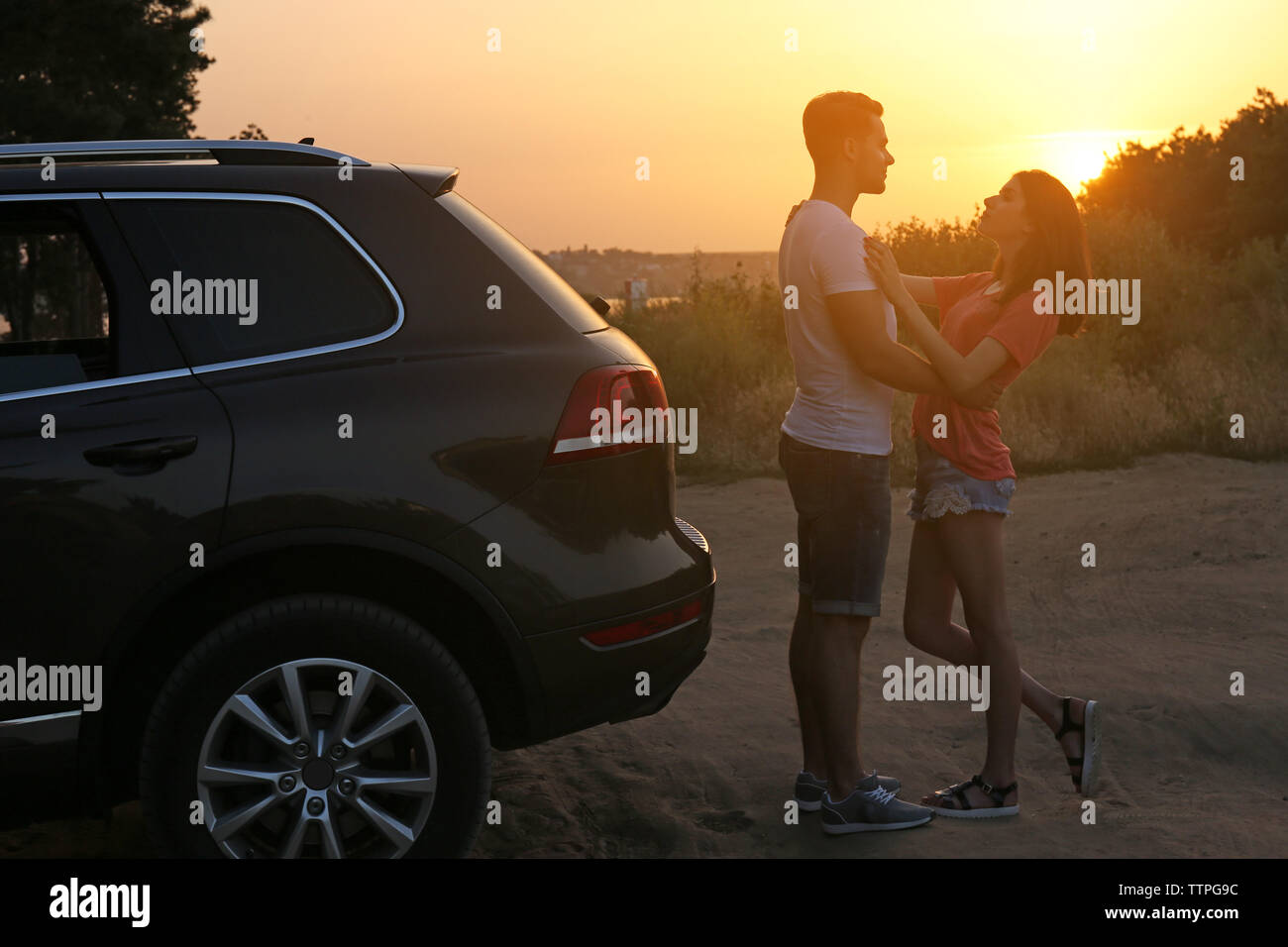 Young couple near car on sunset background - Stock Image