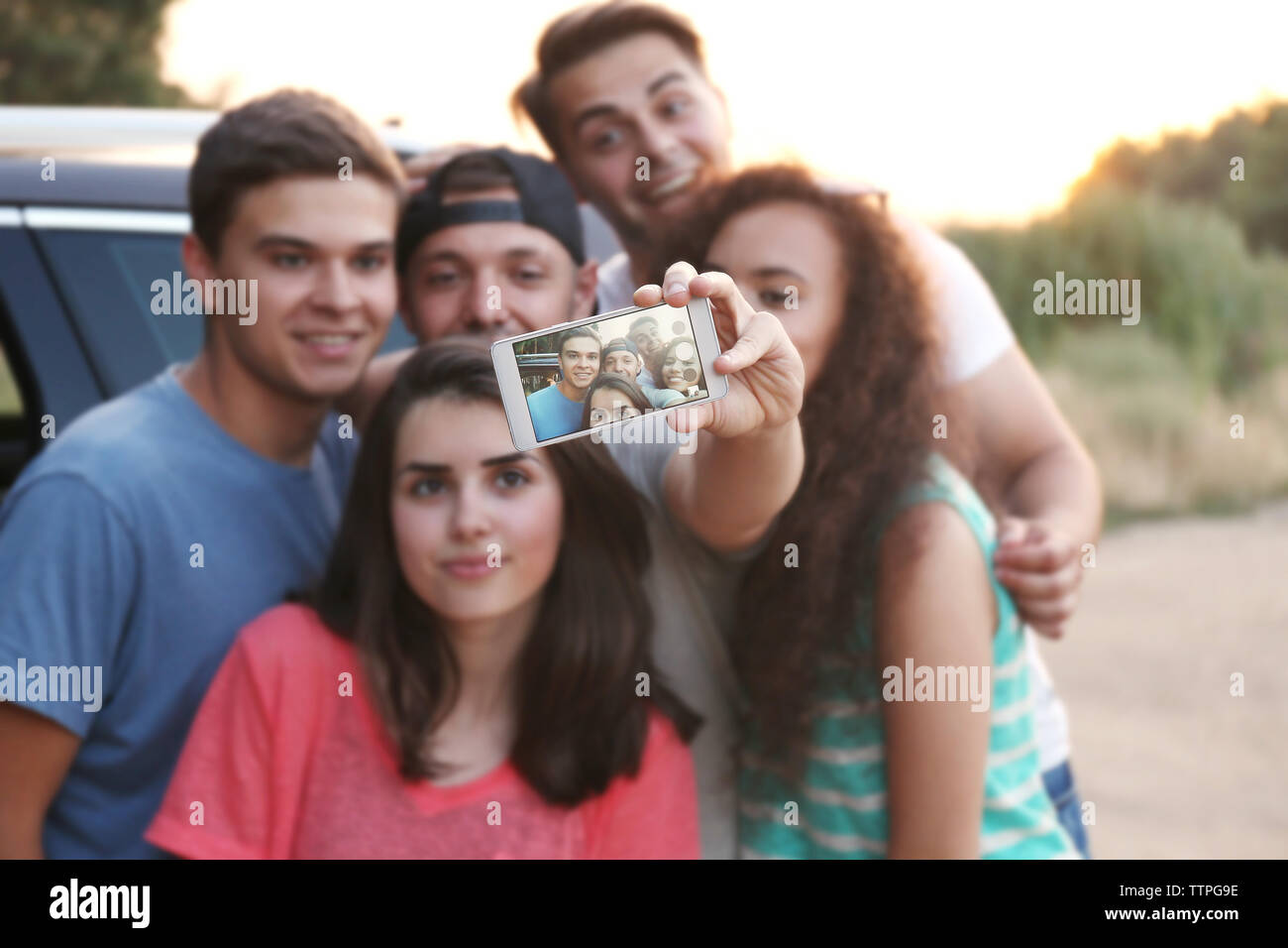 Cheerful friends taking selfie, outdoors - Stock Image