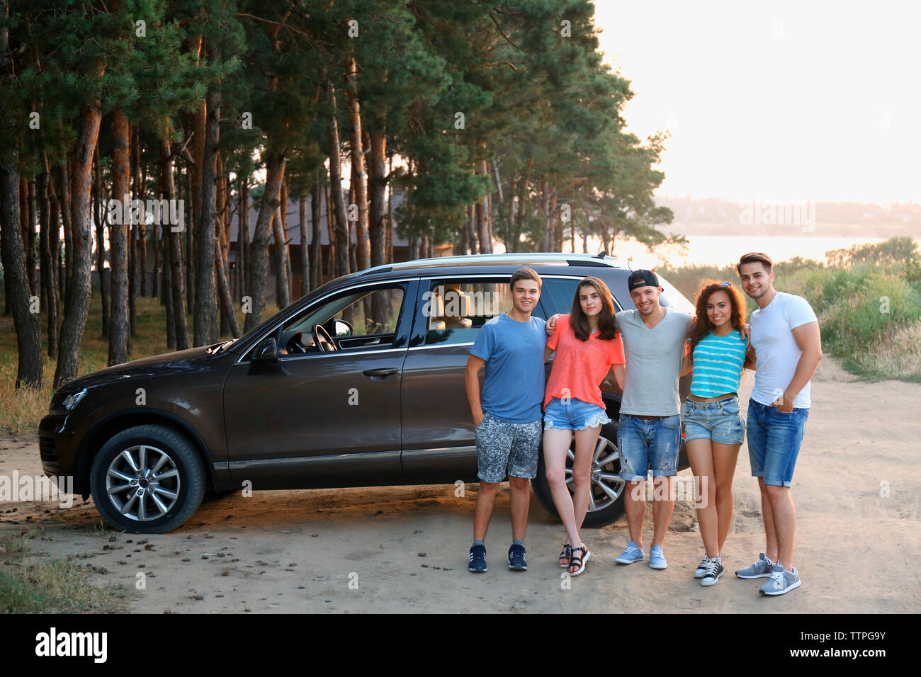 Group of young friends standing near car in the forest - Stock Image
