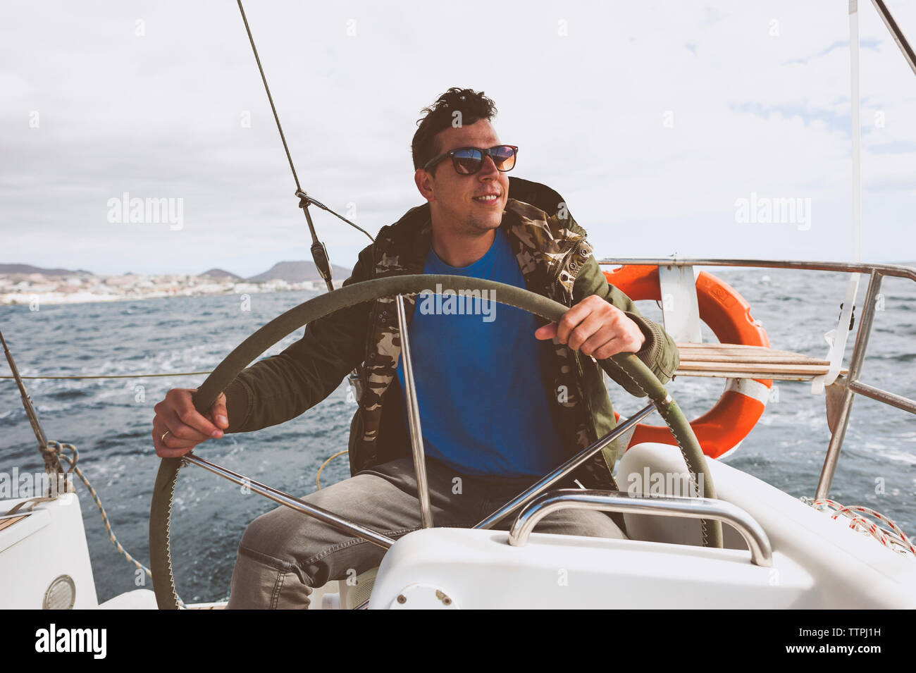Happy man driving nautical vessel on sea against cloudy sky - Stock Image