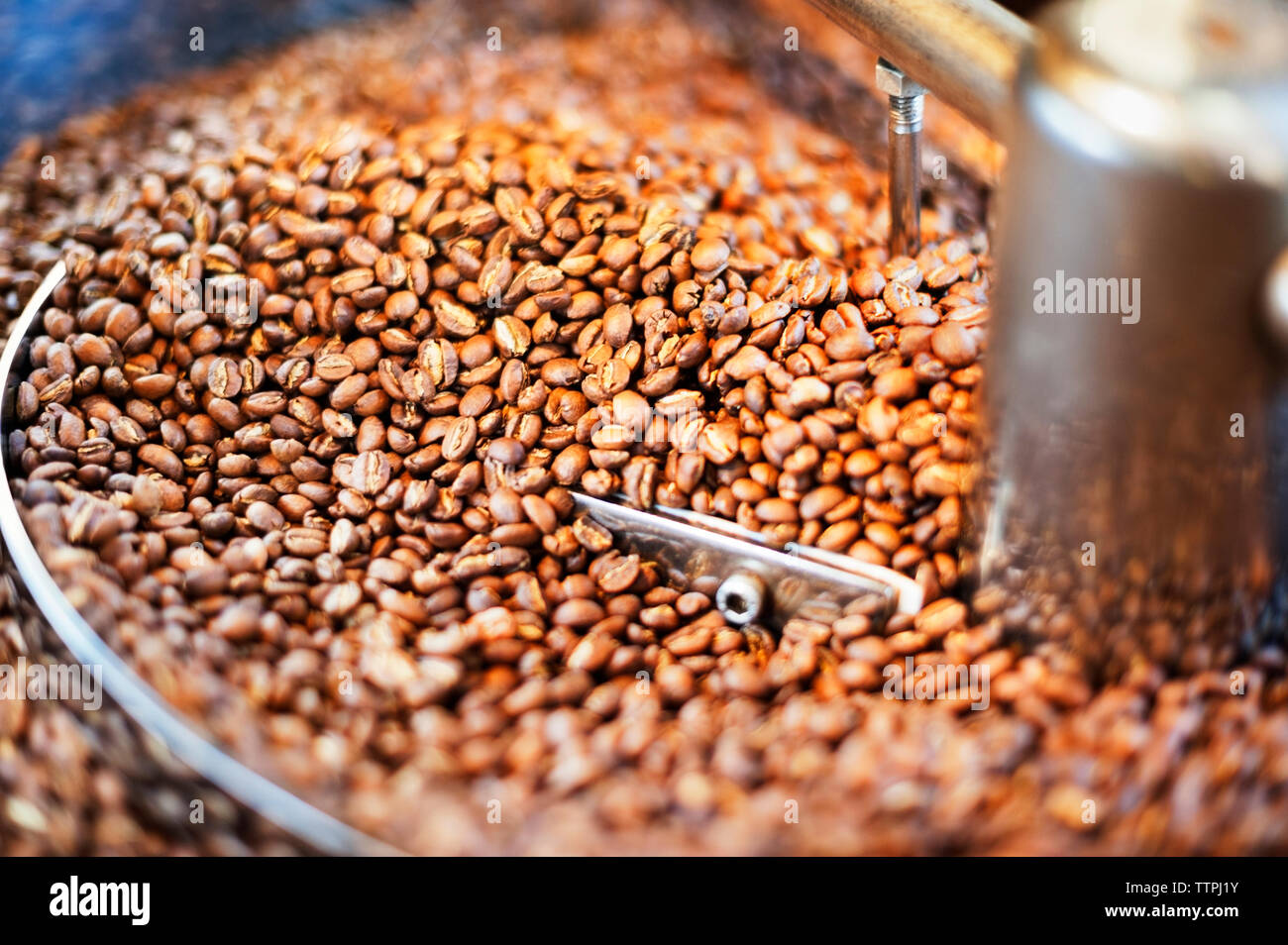 Close up of coffee beans in coffee roaster - Stock Image