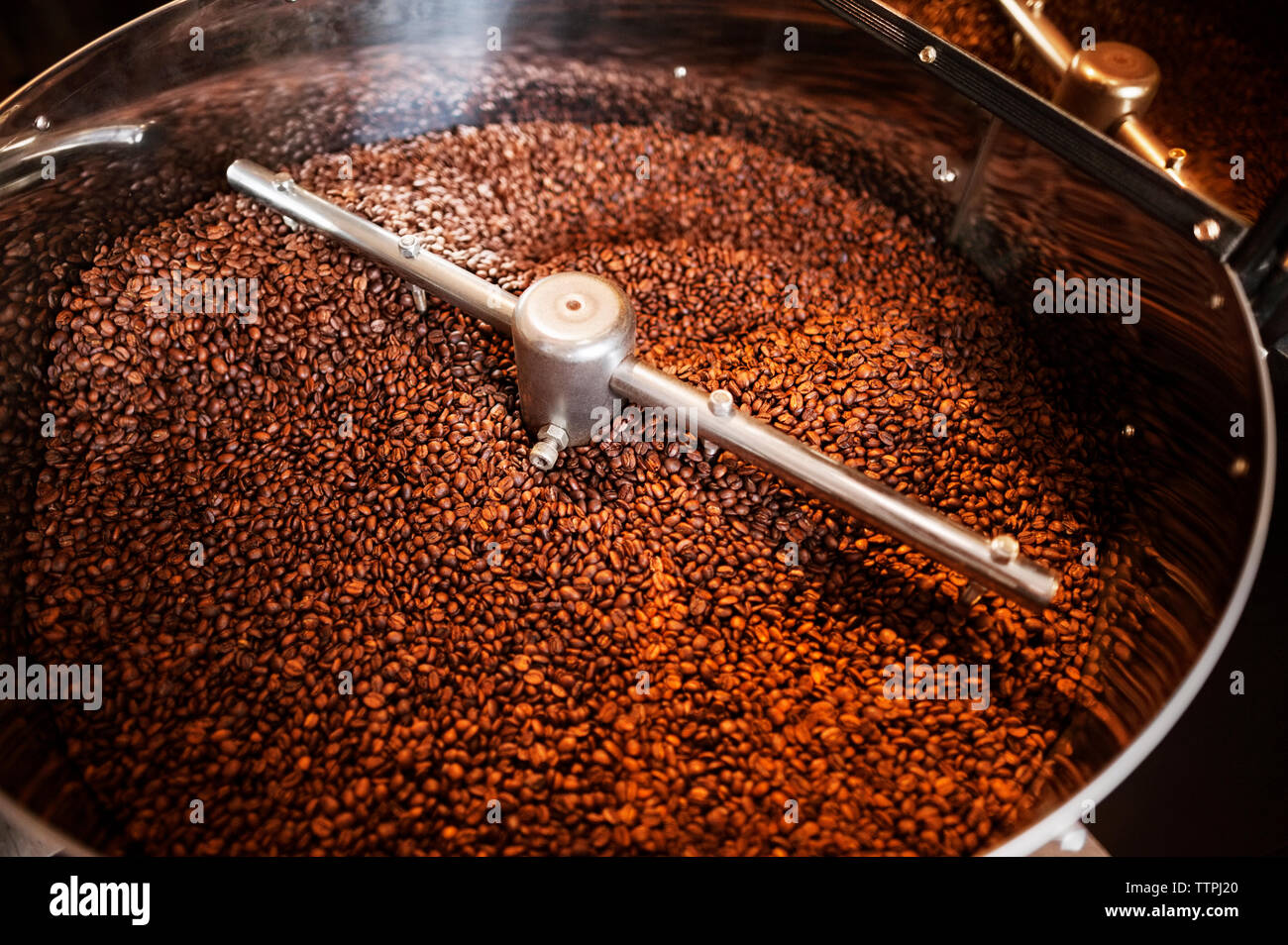 High angle view of coffee beans in coffee roaster - Stock Image