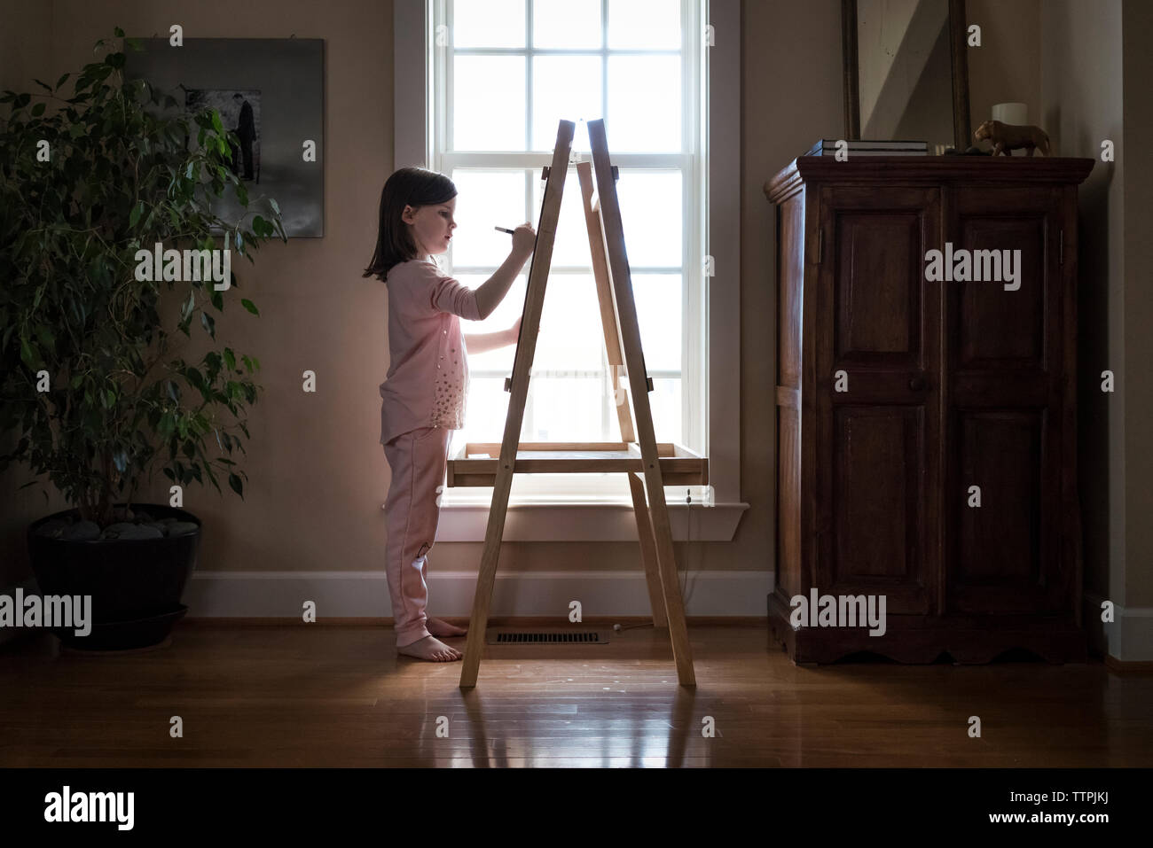 Side view of girl drawing on artist's canvas at home - Stock Image