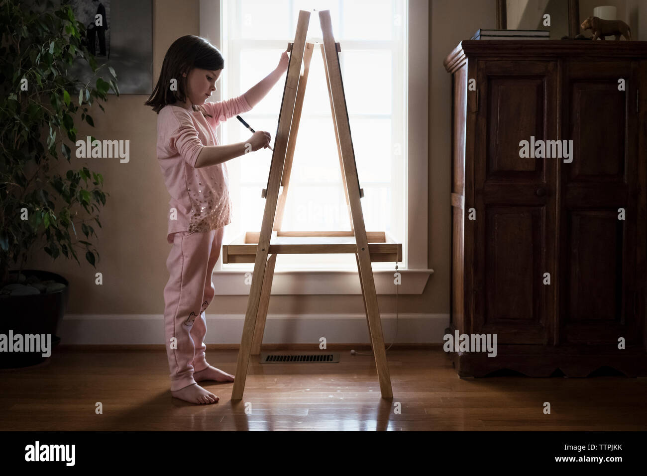 Side view of girl drawing on artist's canvas while standing at home - Stock Image