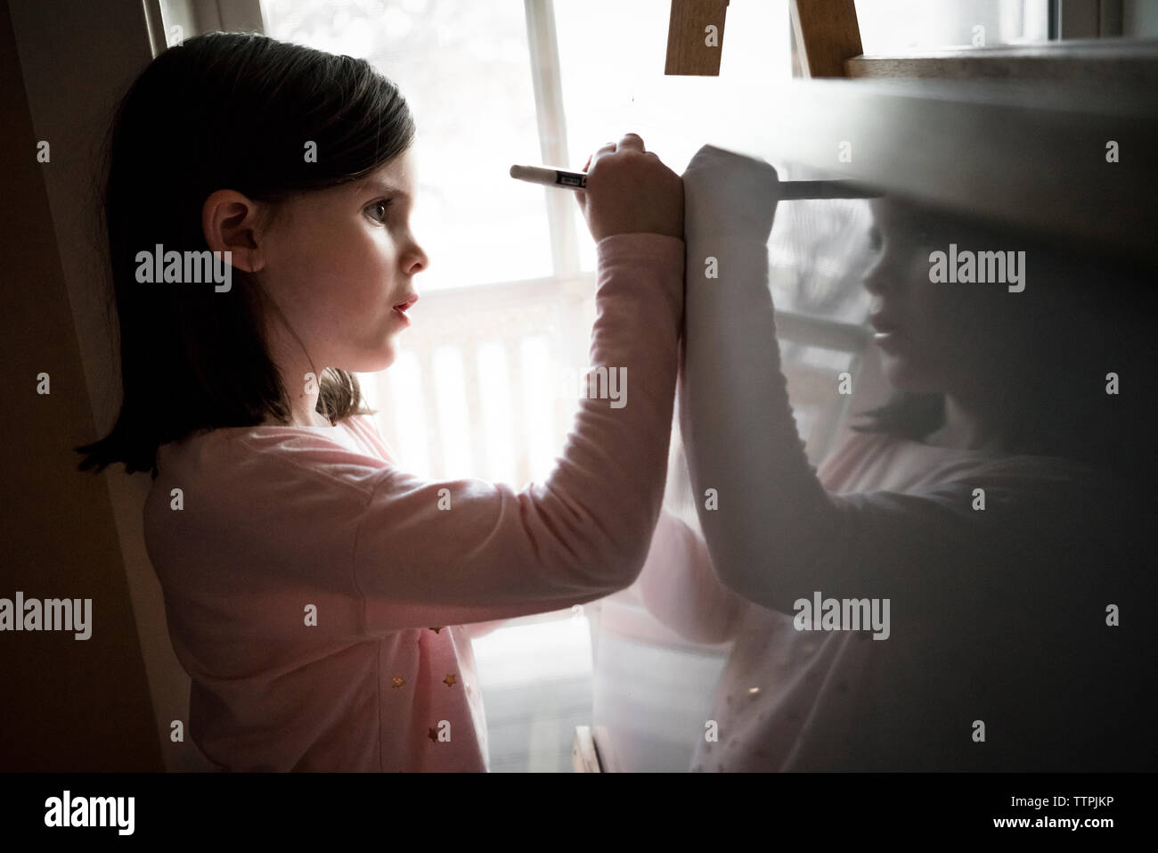 Side view of cute girl drawing on artist's canvas at home - Stock Image