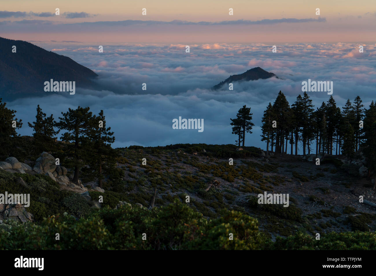 Scenic view of cloudscape by mountain during sunset - Stock Image