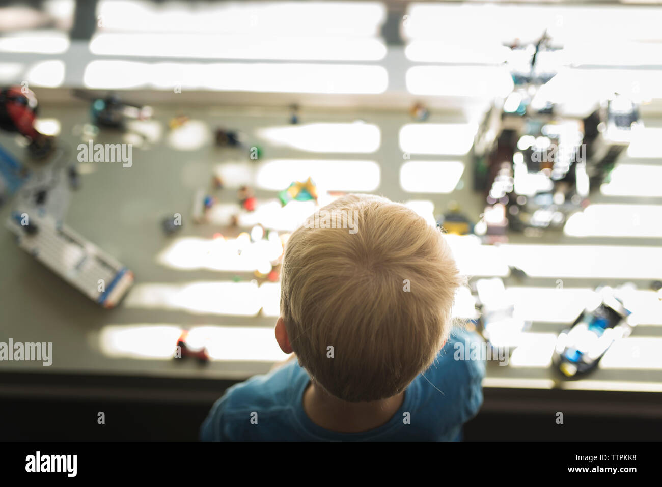 High angle view of boy at home with toys in background - Stock Photo