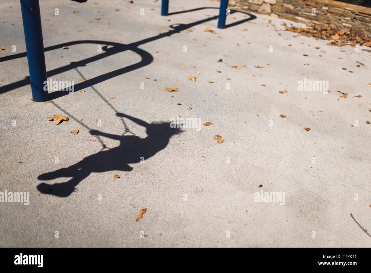 Shadow of boy swinging at park - Stock Image