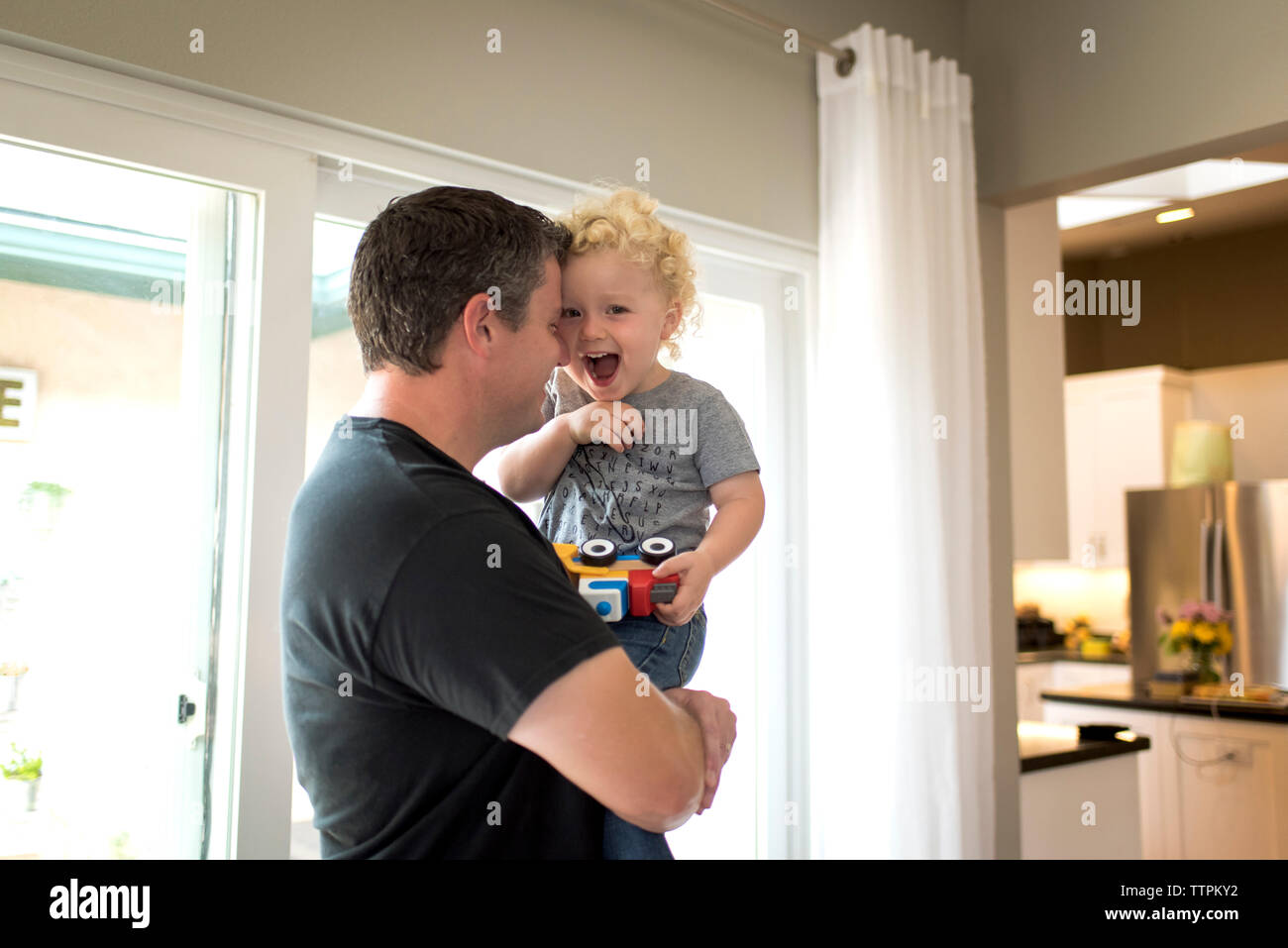 Portrait of cheerful son carried by father at home Stock Photo