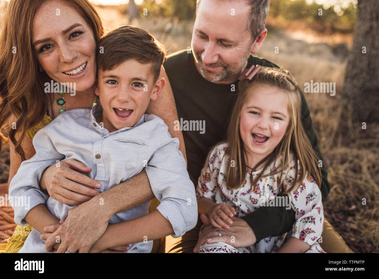 Close up of family laughing while embracing in California field Stock Photo