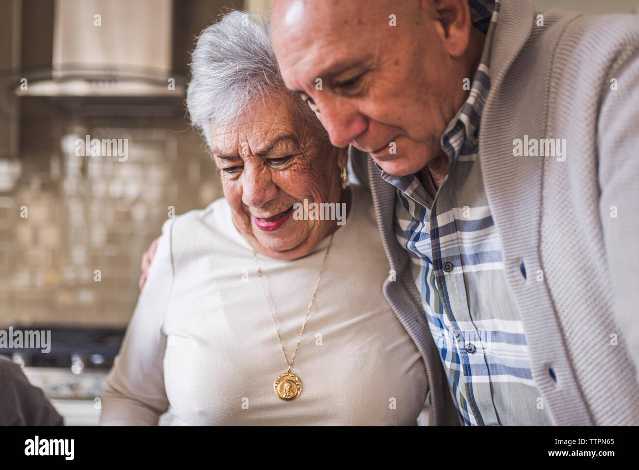 Close of of adult son hugging senior mother in kitchen Stock Photo