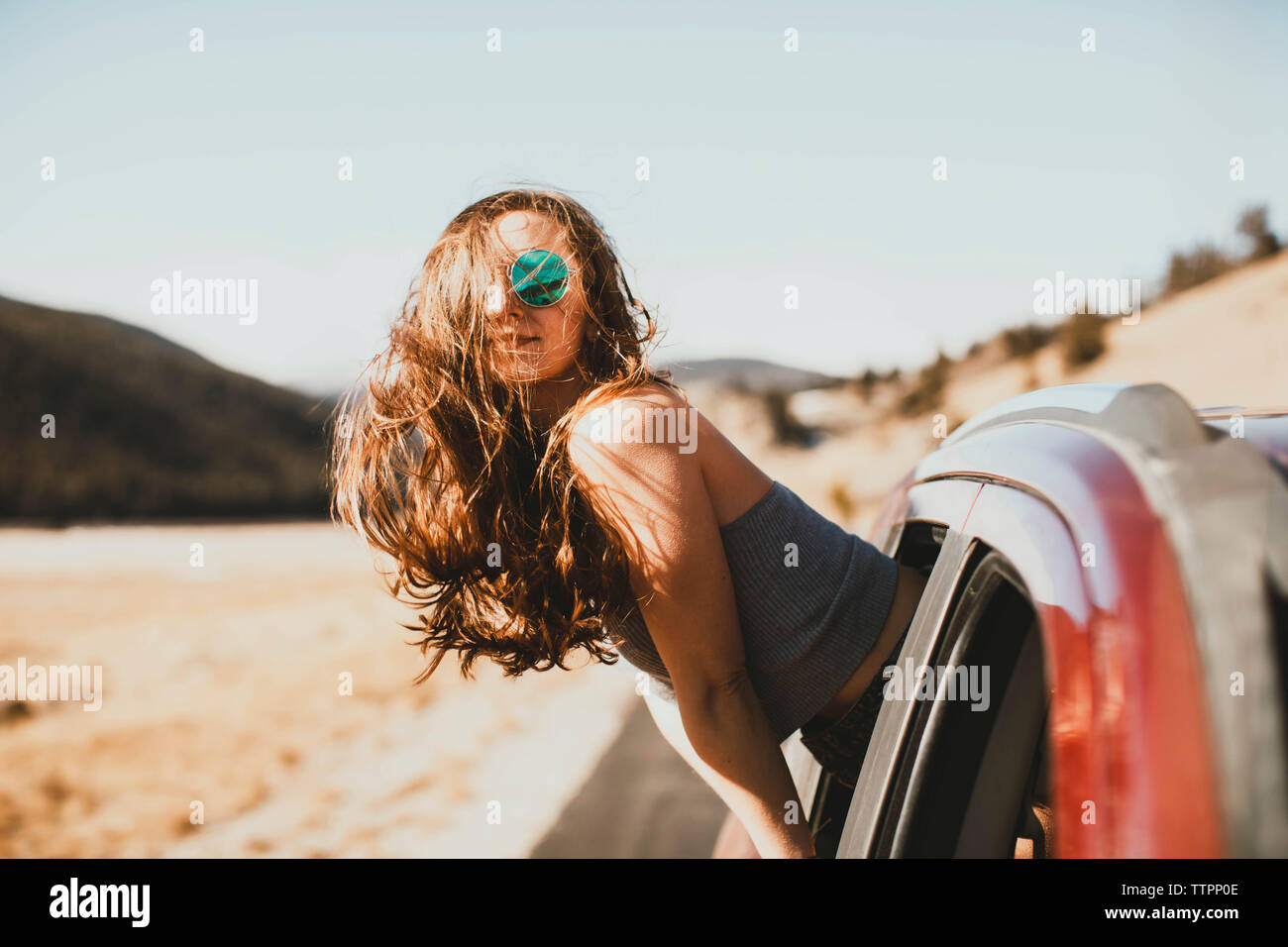 Side view of young woman with tousled hair leaning out from car window - Stock Image