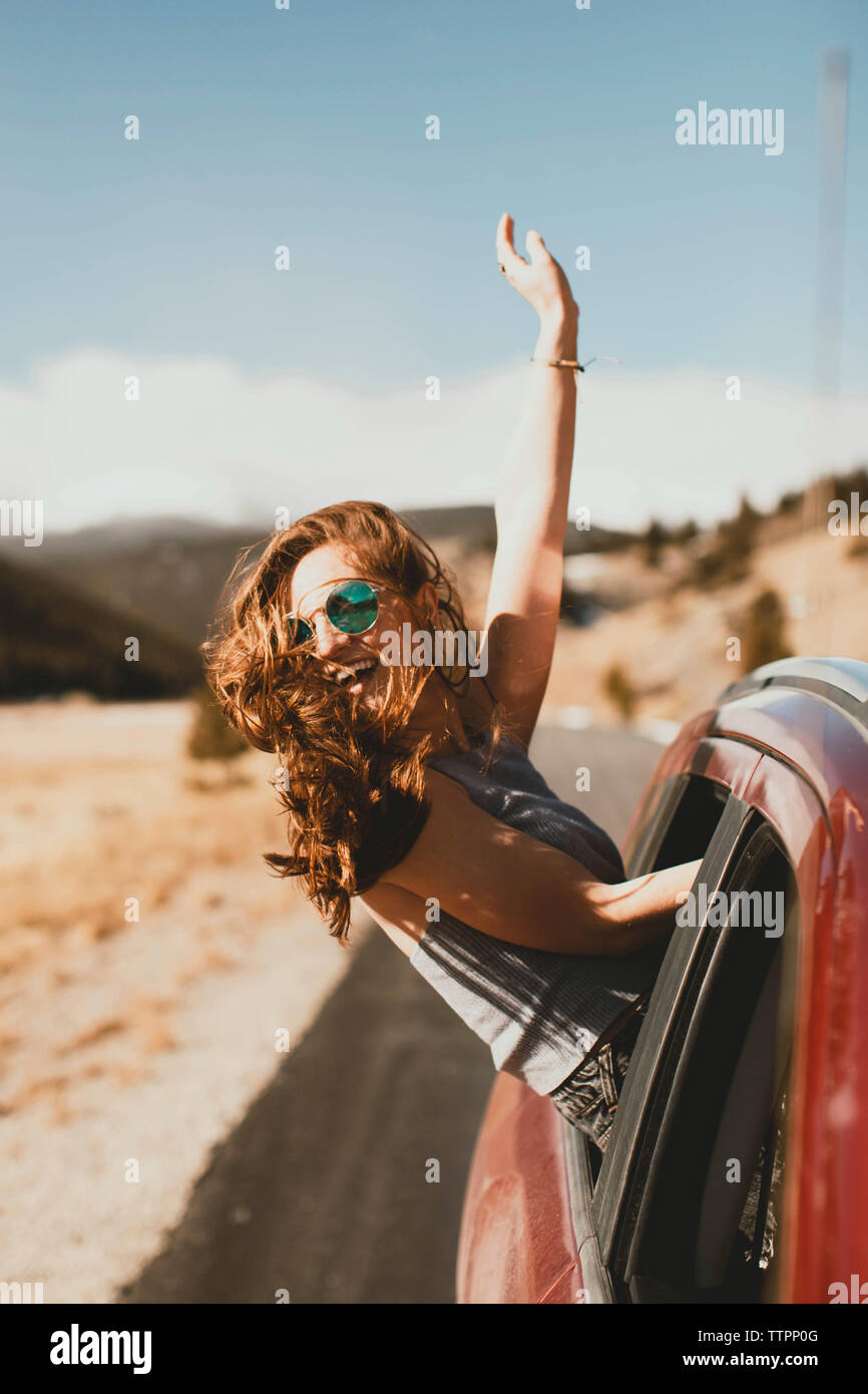 Cheerful young woman with tousled hair leaning out from car window - Stock Image