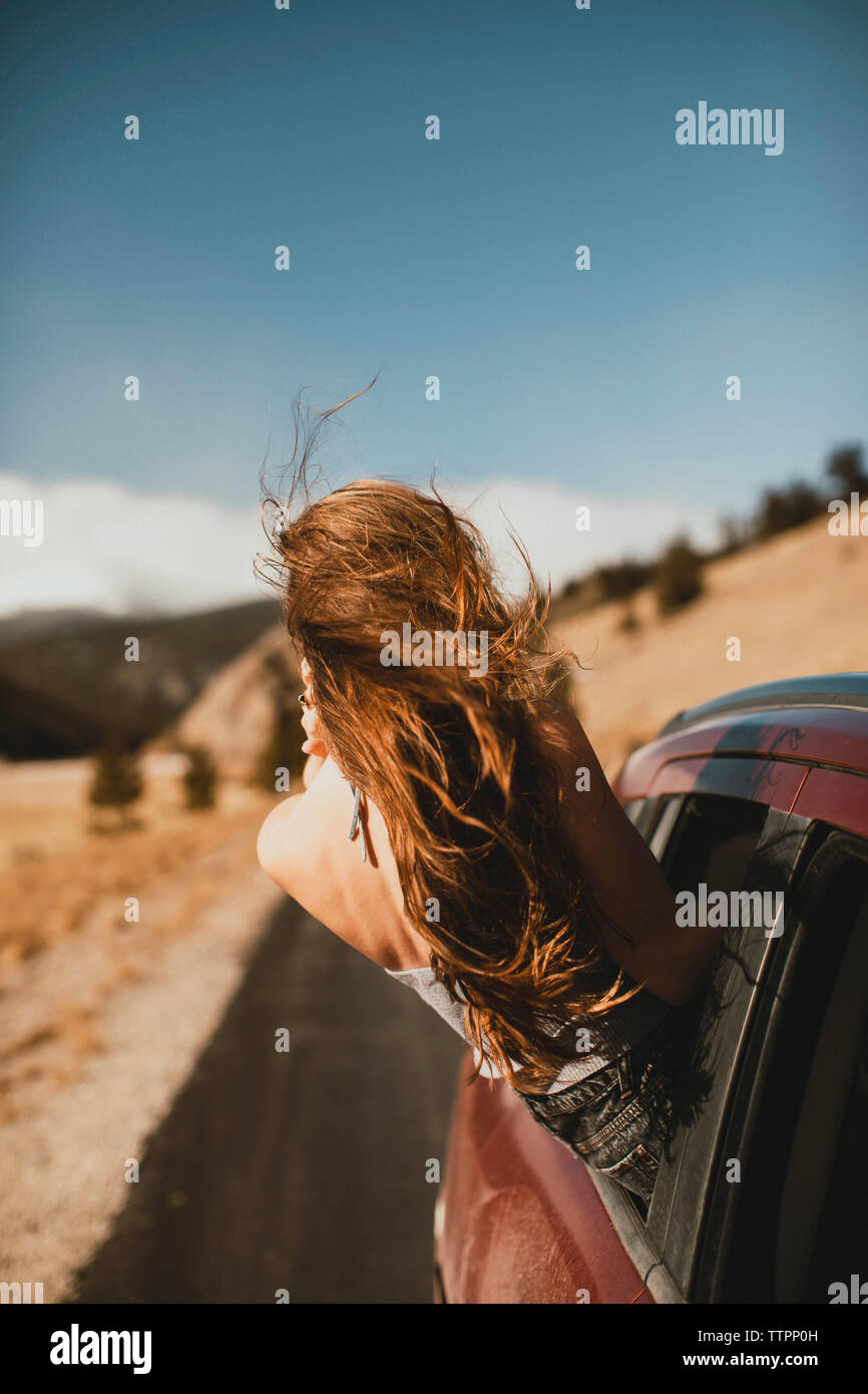 Carefree young woman with tousled hair leaning out from car window - Stock Image
