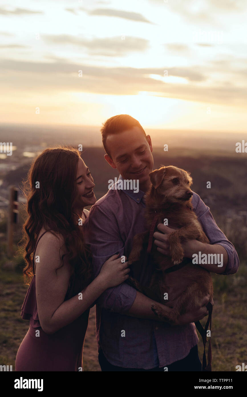 Young couple with dog standing on field during sunset - Stock Image