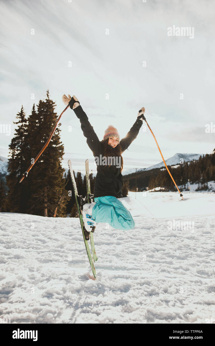 Excited young woman jumping while skiing on snowy field - Stock Image