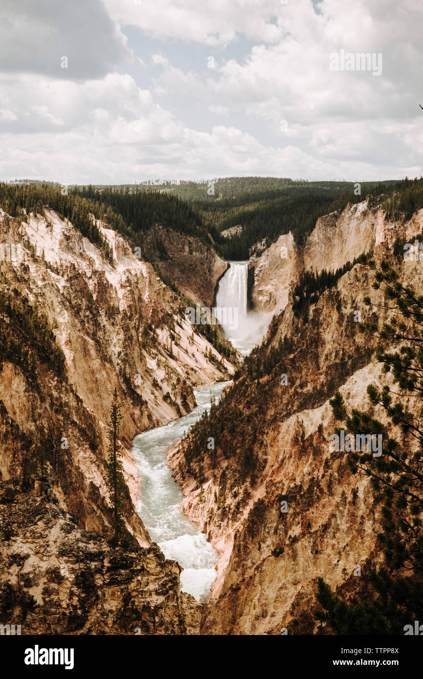 Scenic view Of Yellowstone Falls Against Cloudy Sky In forest Stock Photo