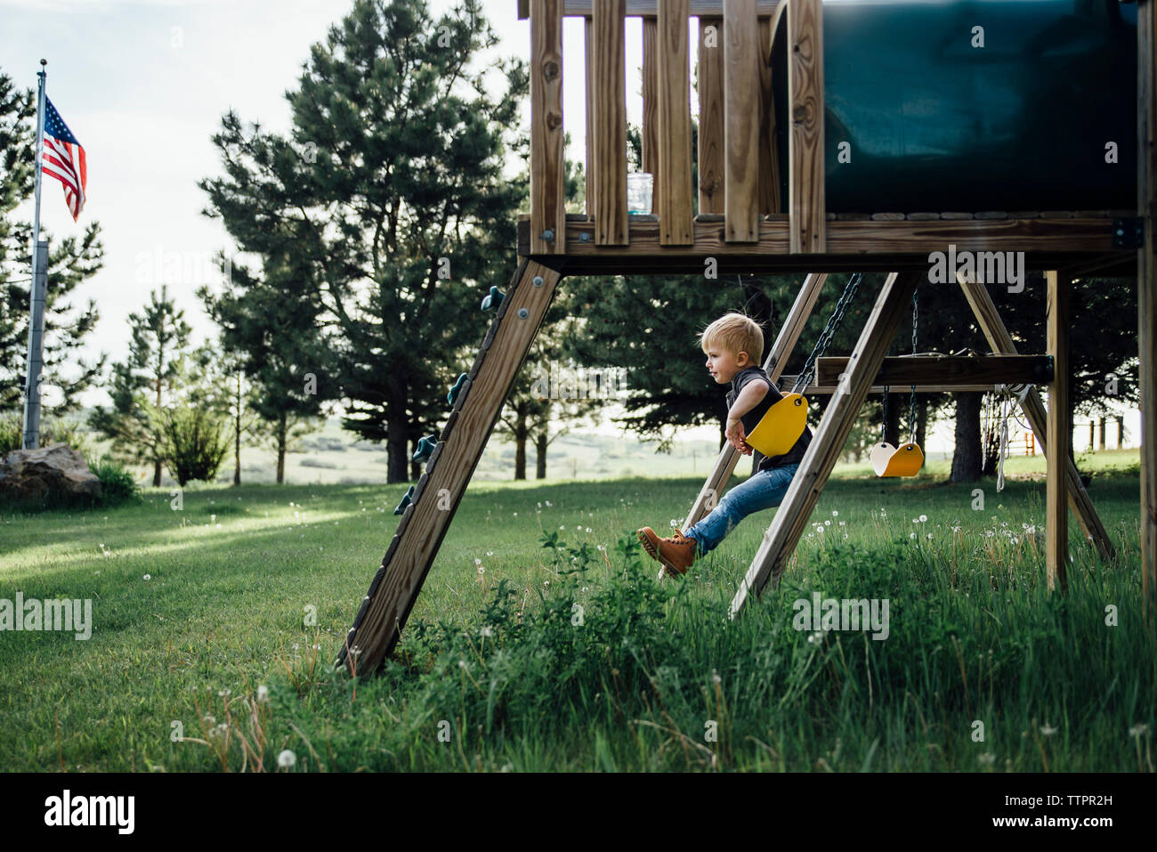 Side view of boy swinging at park - Stock Image