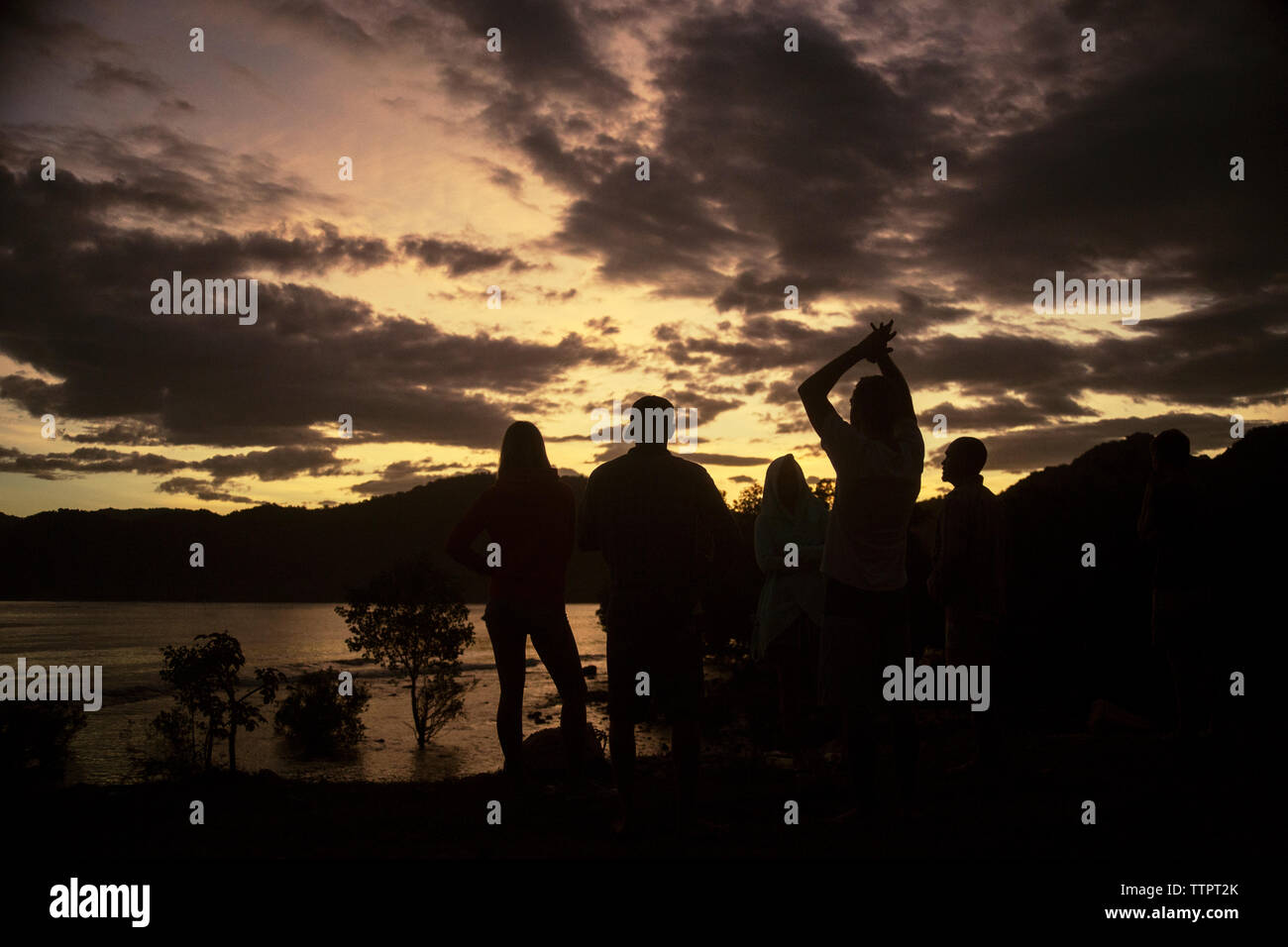 Silhouette friends enjoying at lakeshore against cloudy sky during sunset - Stock Image