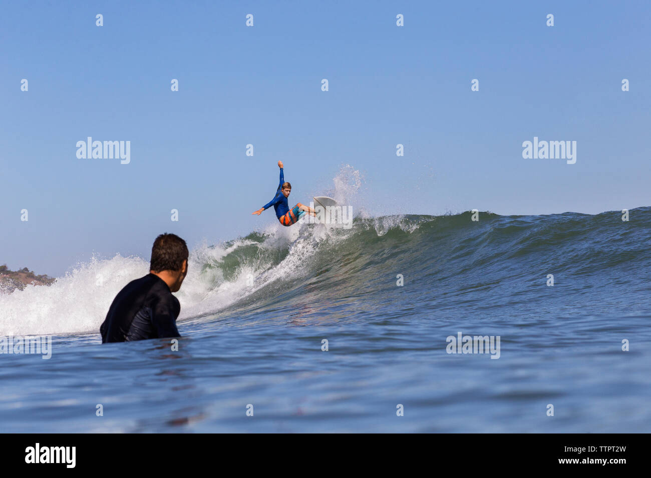Man looking at friend surfing on sea against clear blue sky - Stock Image