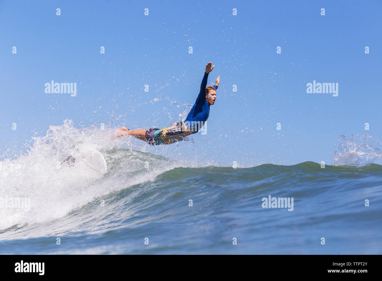Side view of male surfer jumping on sea against clear blue sky - Stock Image