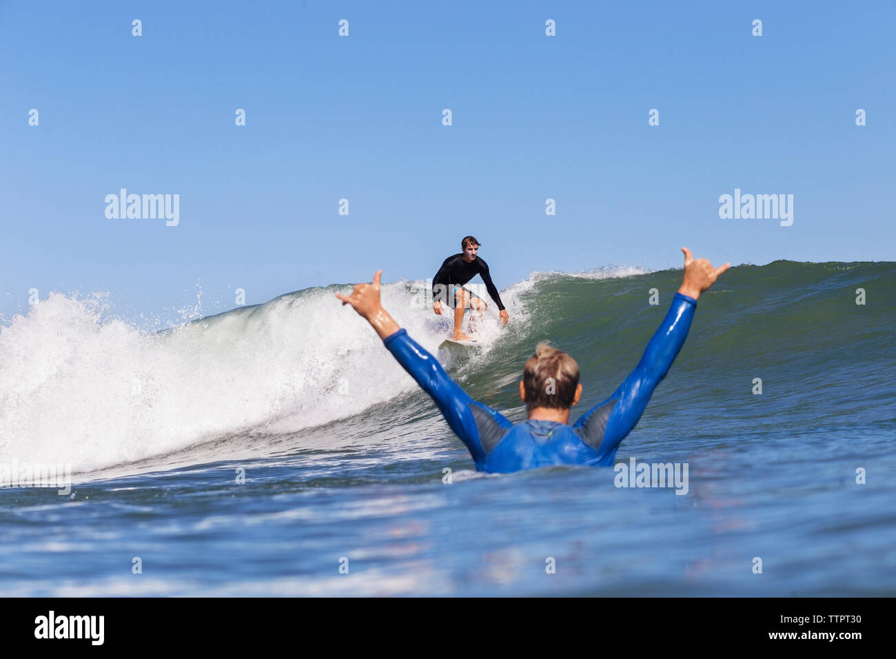 Man cheering while looking at friend surfing on sea against clear blue sky - Stock Image