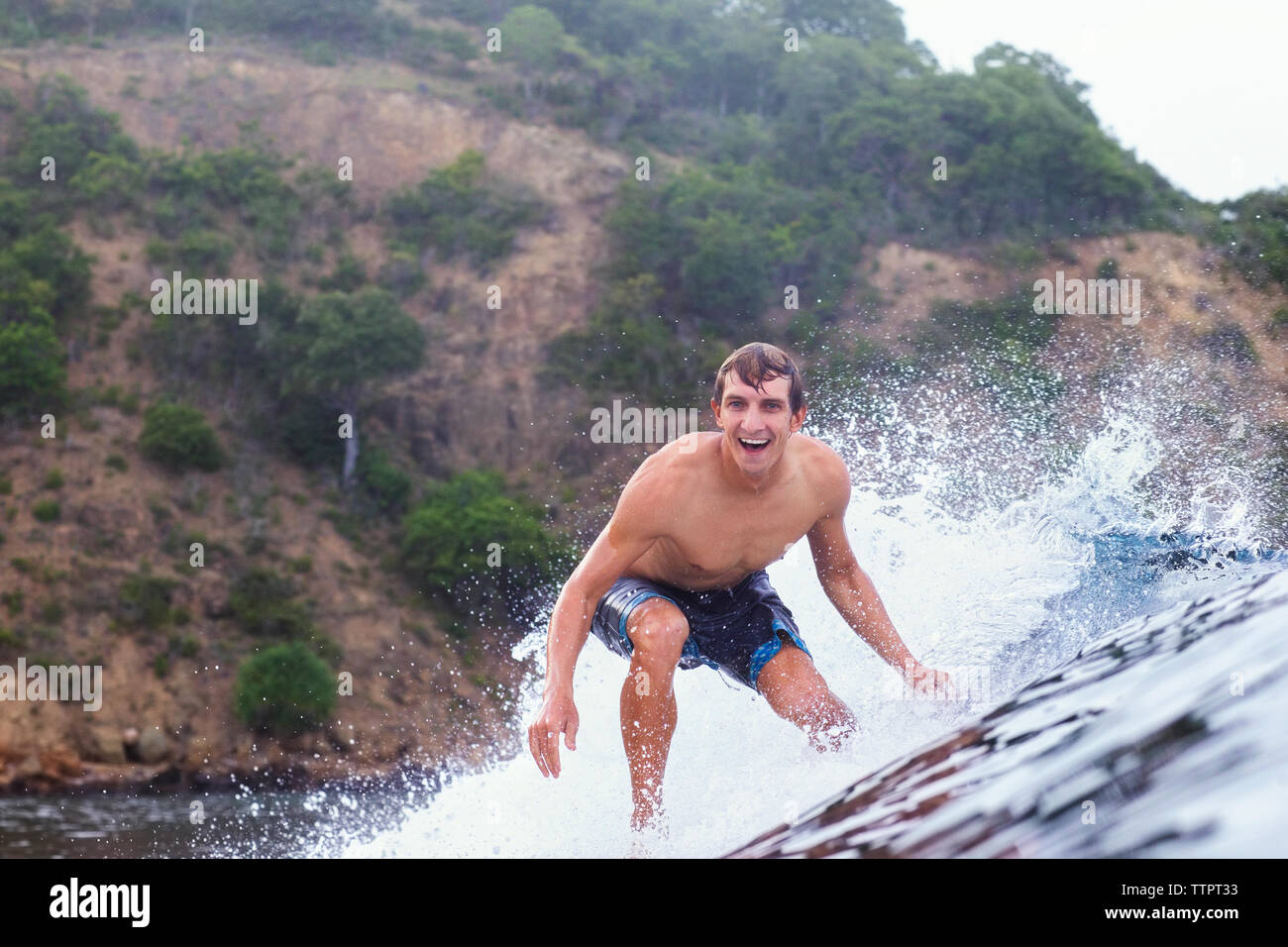 Cheerful man surfing on sea - Stock Image