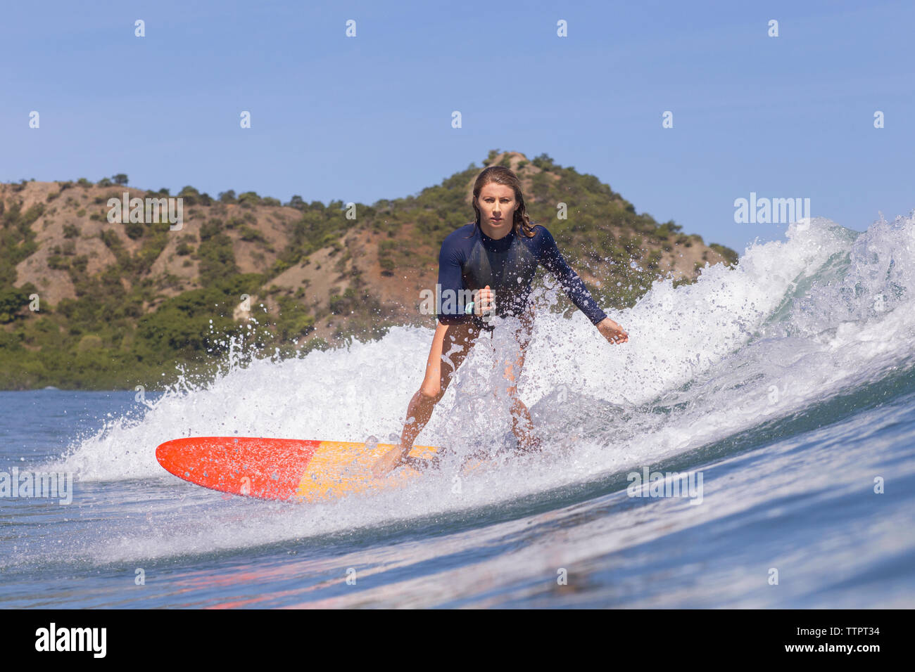 Confident woman surfing on sea against clear blue sky - Stock Image