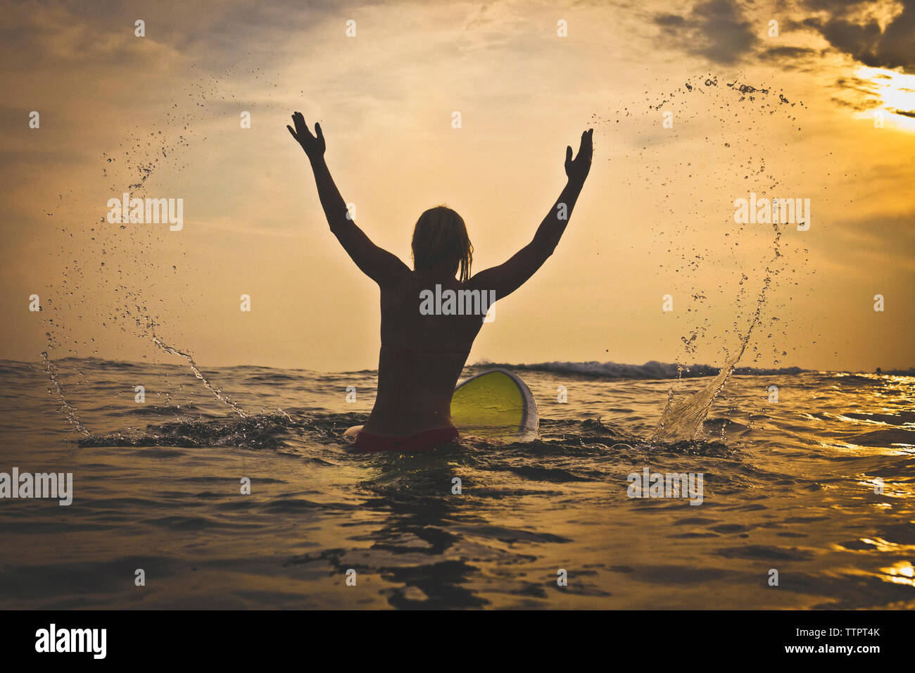 Rear view of playful woman splashing water while sitting on surfboard in sea - Stock Image