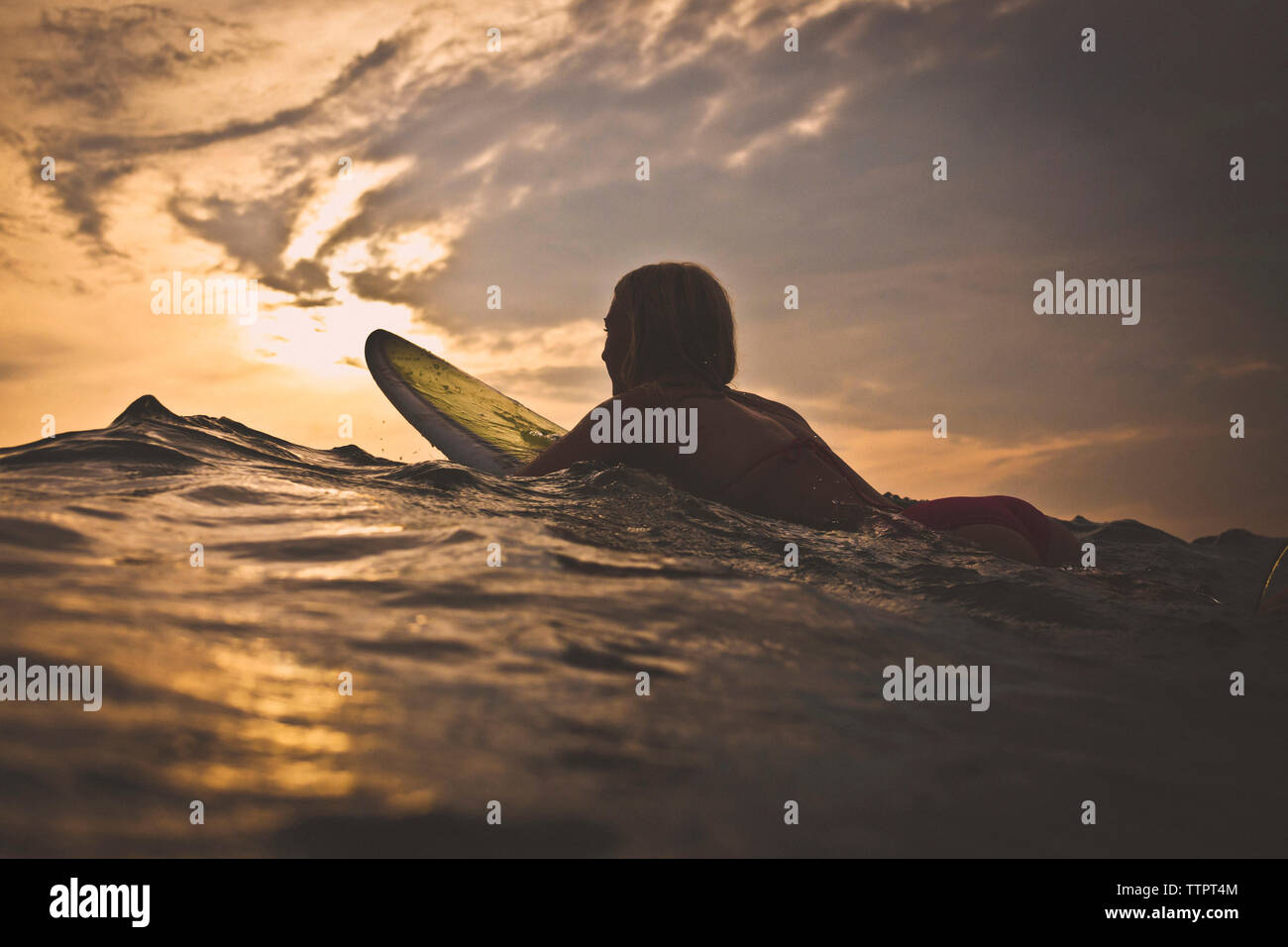 Woman surfing in sea against sky during sunset - Stock Image