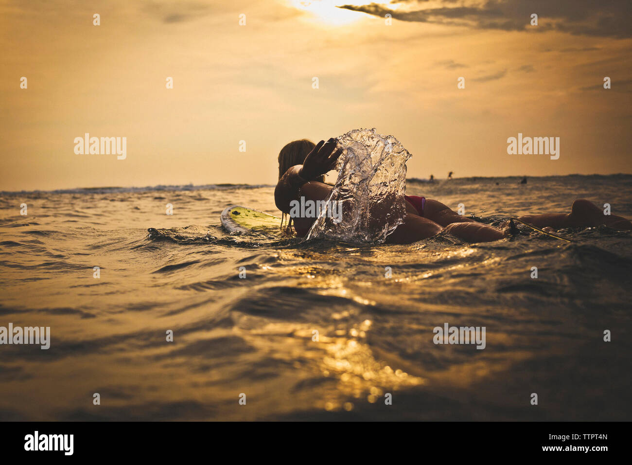 Woman surfing in sea against sky - Stock Image