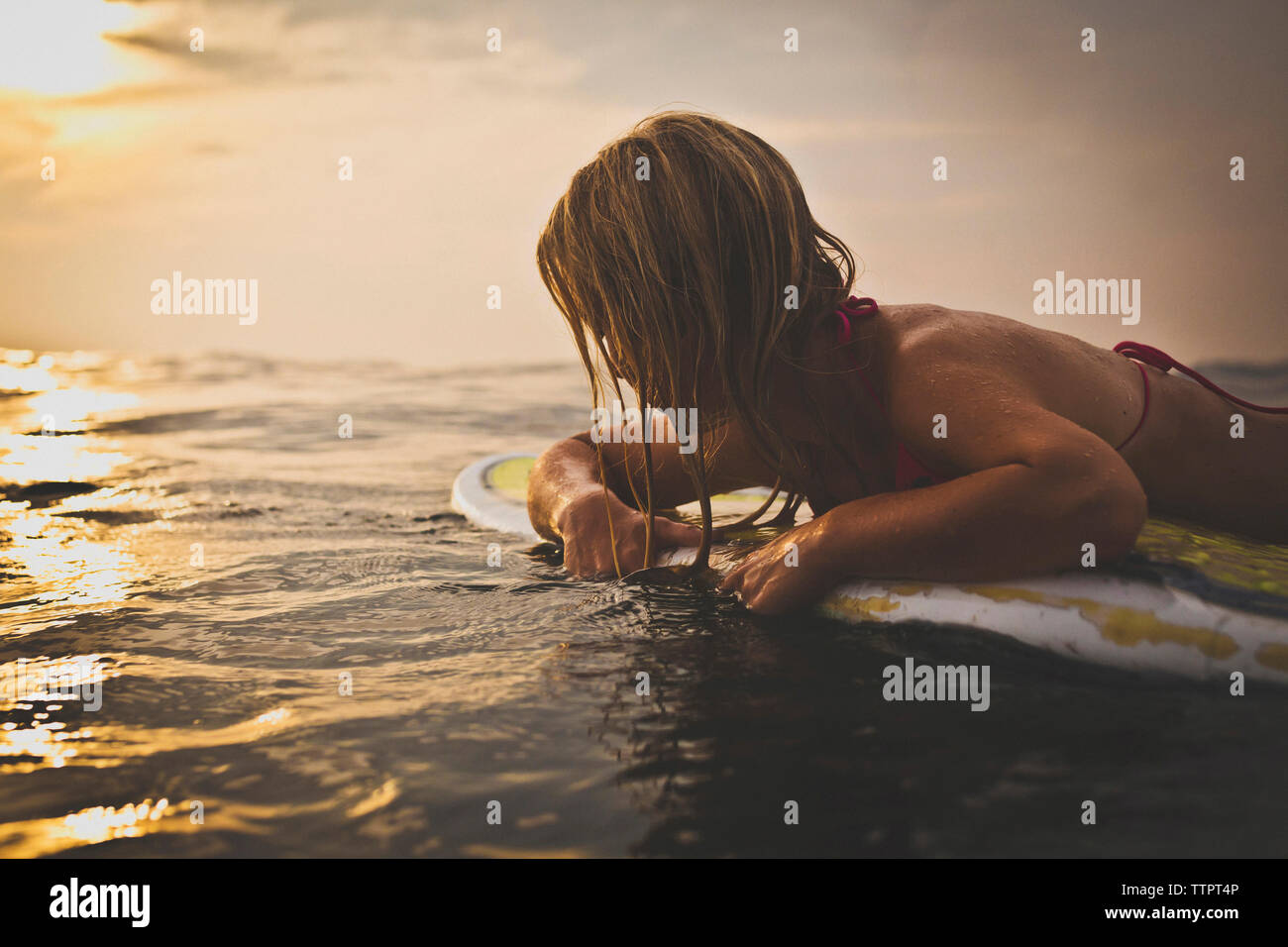 Woman lying on surfboard in sea against sky - Stock Image