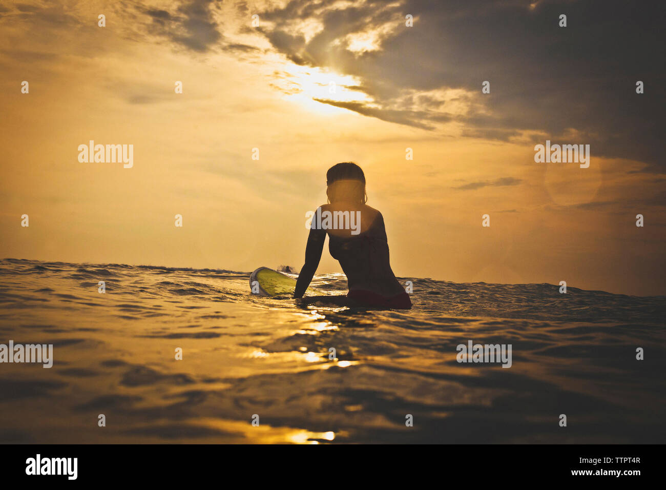 Woman sitting on surfboard in sea against sky - Stock Image
