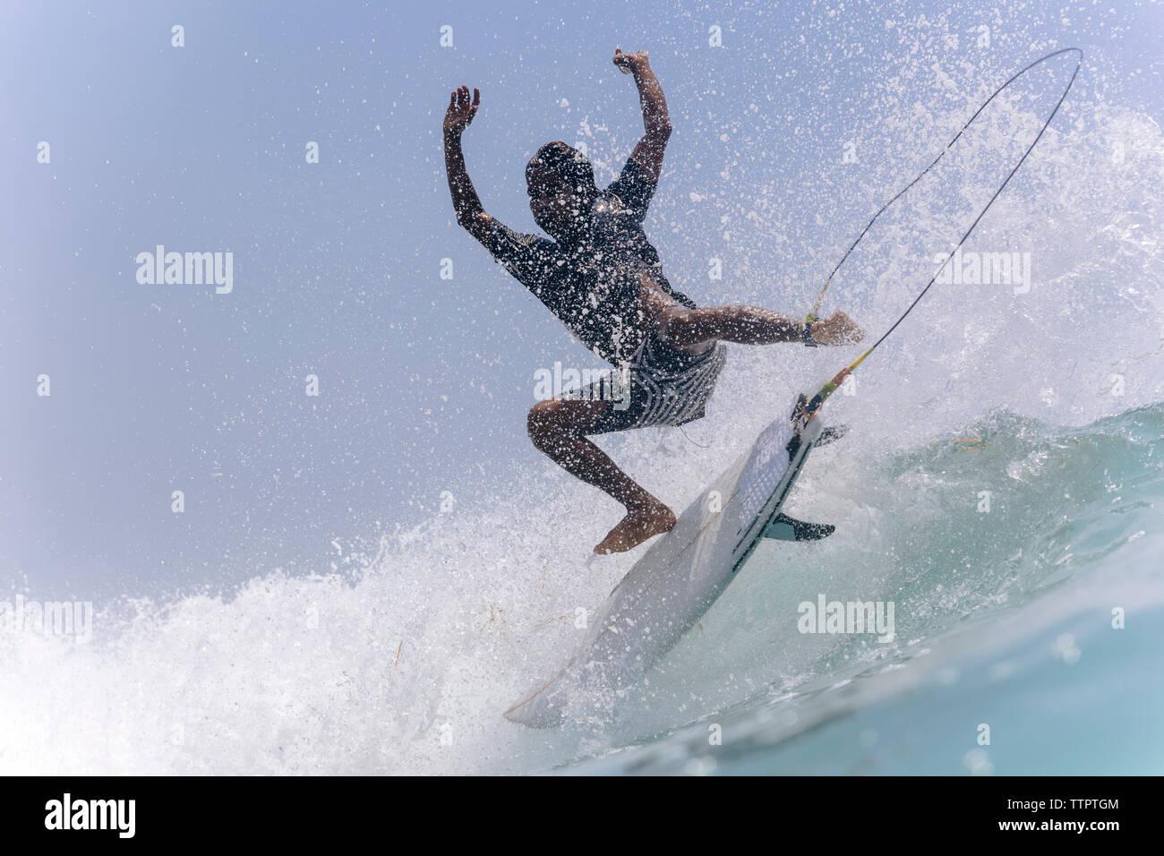 Full length of man surfing in sea against sky - Stock Image