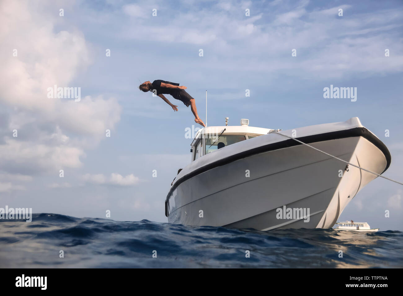 Low angle view of man diving into sea from yacht against cloudy sky Stock Photo
