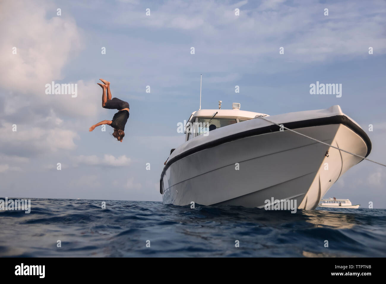 Low angle view of man diving into sea from yacht against cloudy sky at Maldives Stock Photo