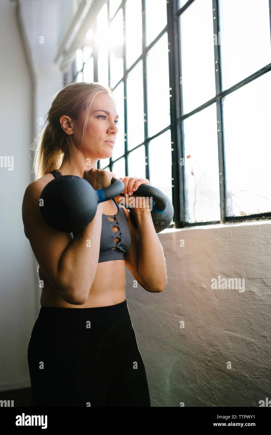 Confident athlete carrying kettlebells while standing by window in gym - Stock Image