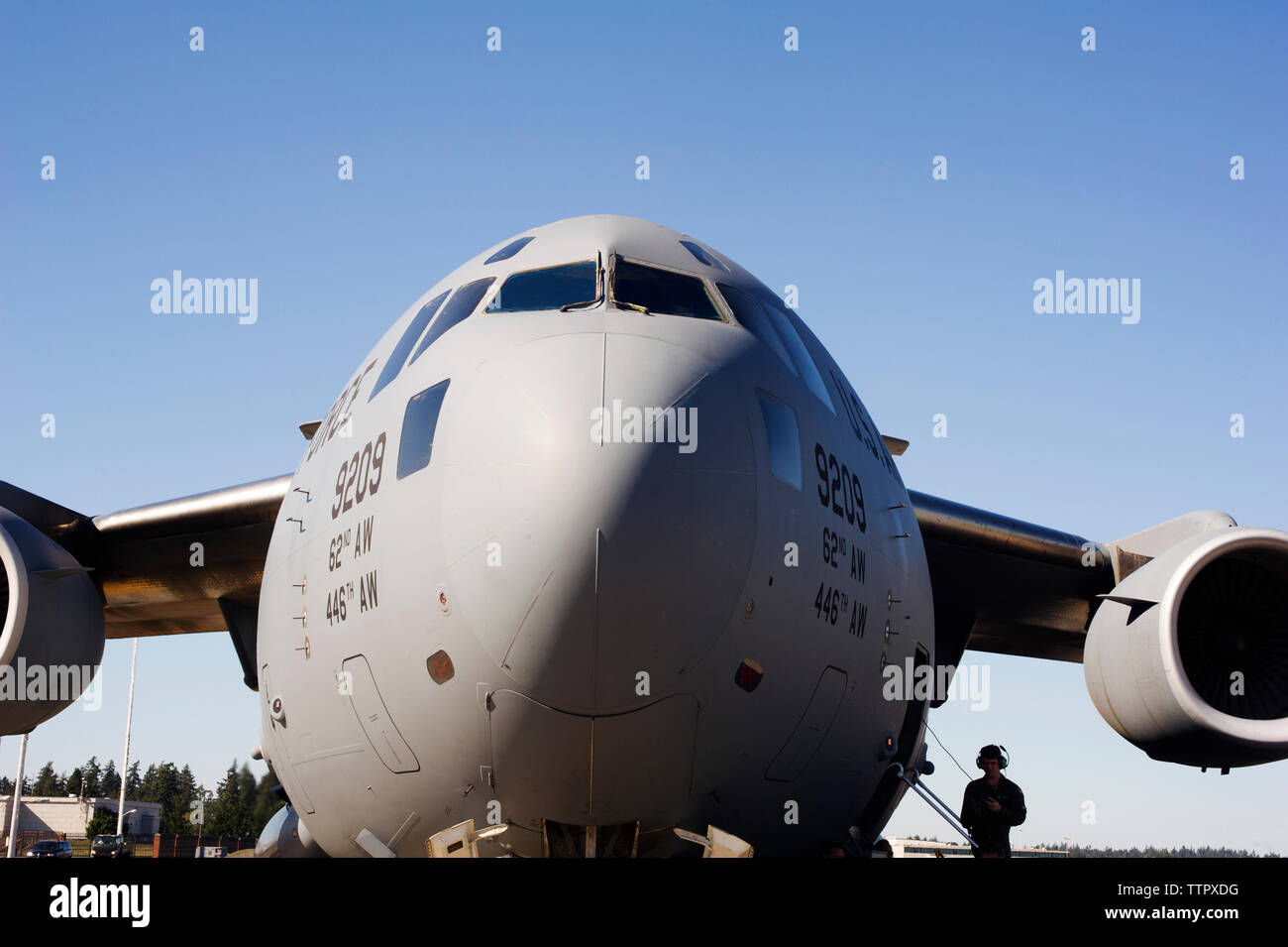 Military airplane on runway against clear blue sky - Stock Image