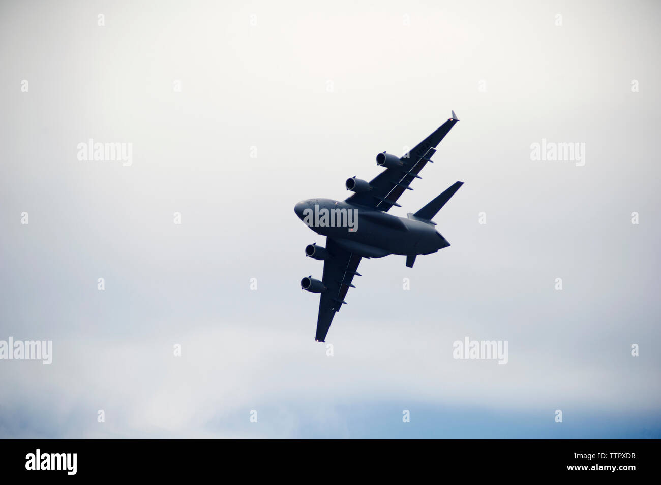 Low angle view of military airplane flying in sky - Stock Image