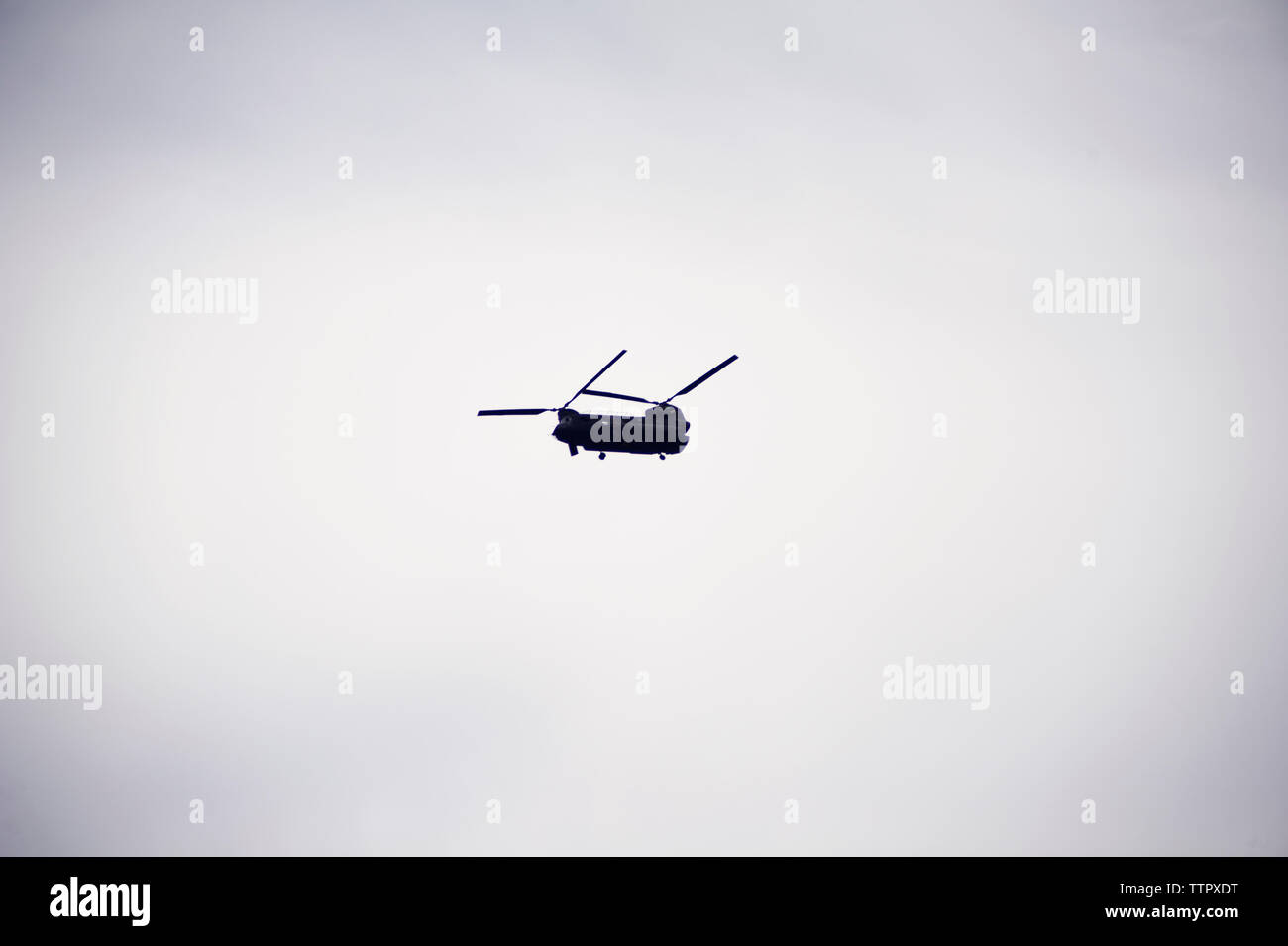 Low angle view of military helicopter flying in clear sky - Stock Image