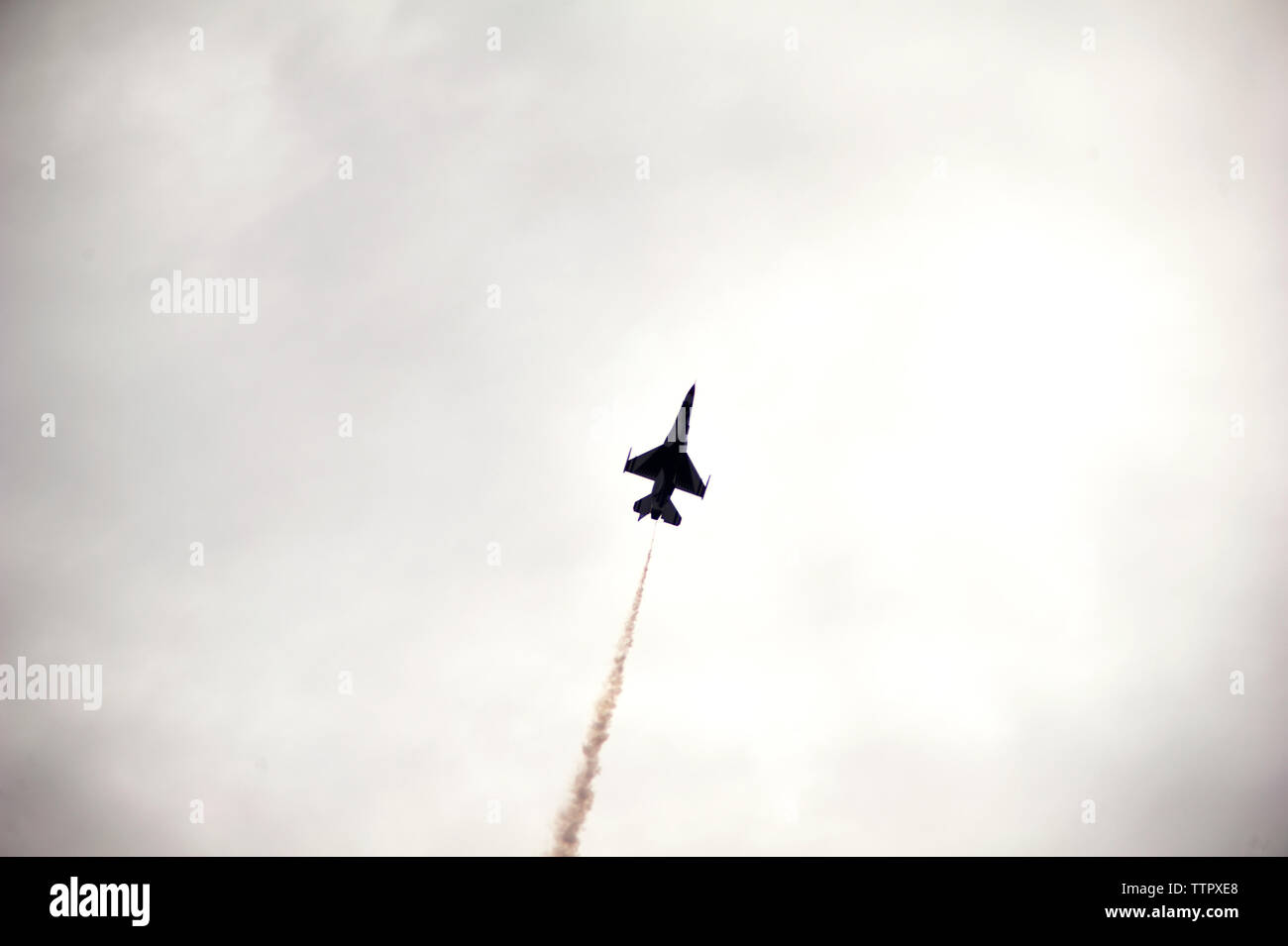 Low angle view of military airplane flying in cloudy sky - Stock Image