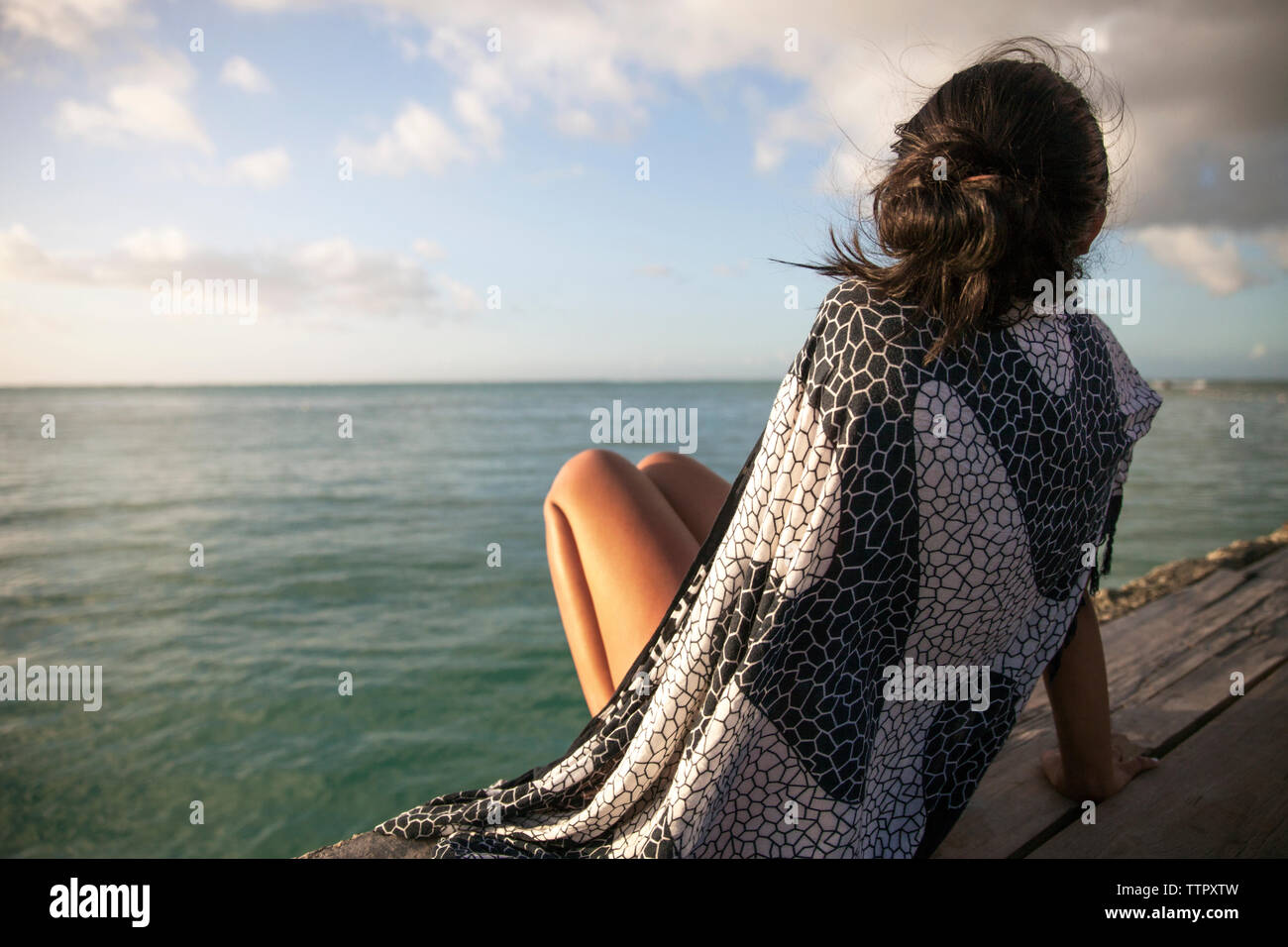 Rear view of woman wrapped in blanket relaxing on boardwalk by sea - Stock Image