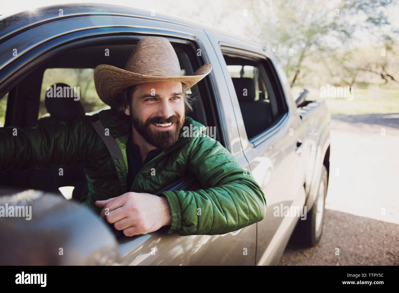 Happy man sitting in pick-up truck on road - Stock Image