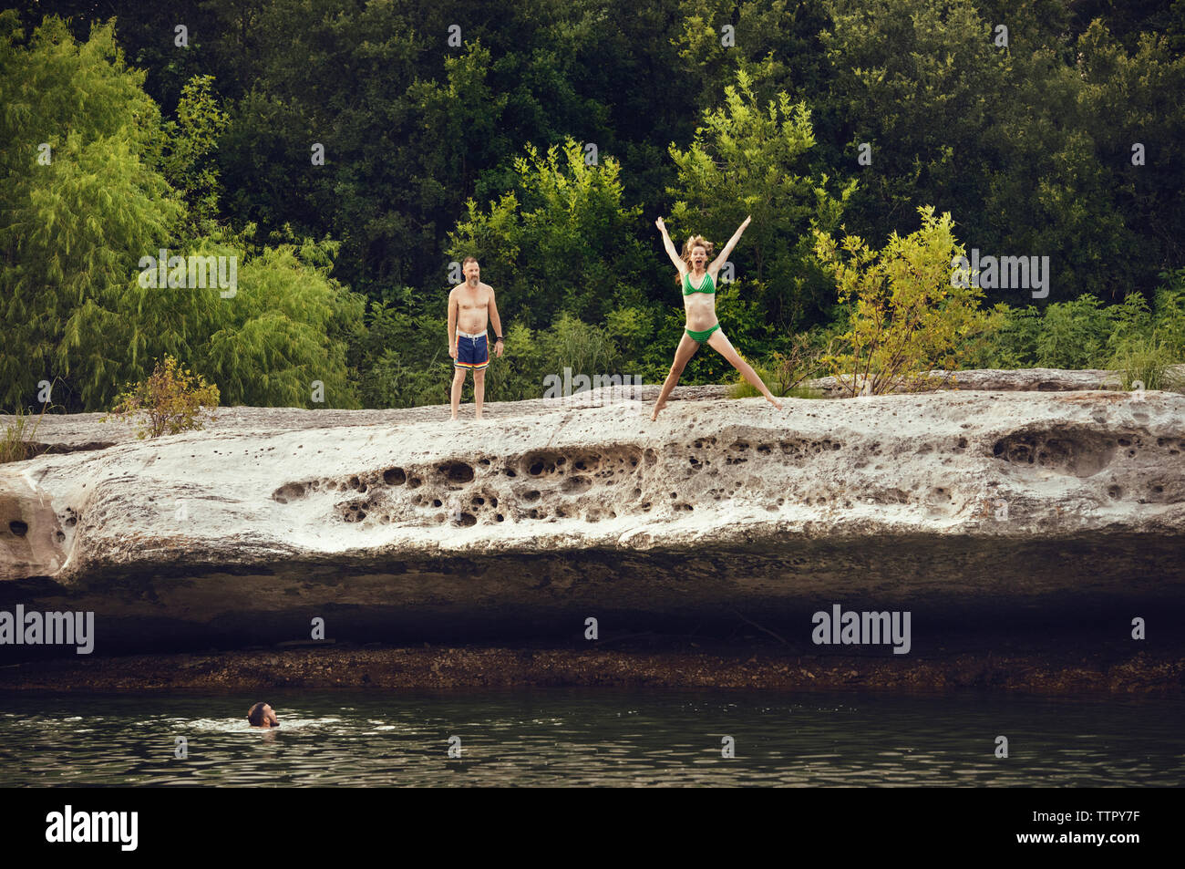 woman and friends jumping in river - Stock Image