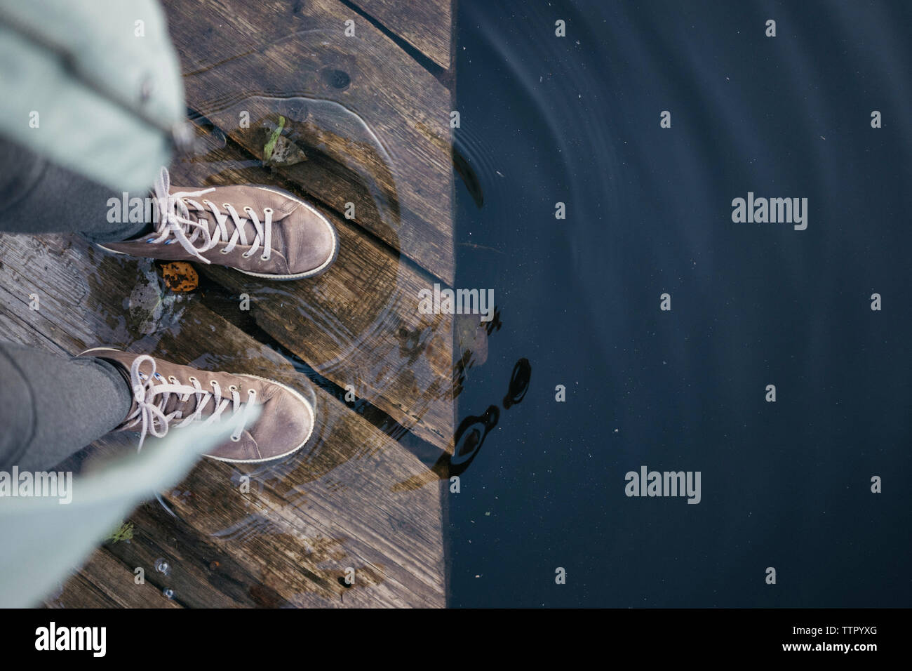 Low section of woman standing on pier over lake in forest Stock Photo