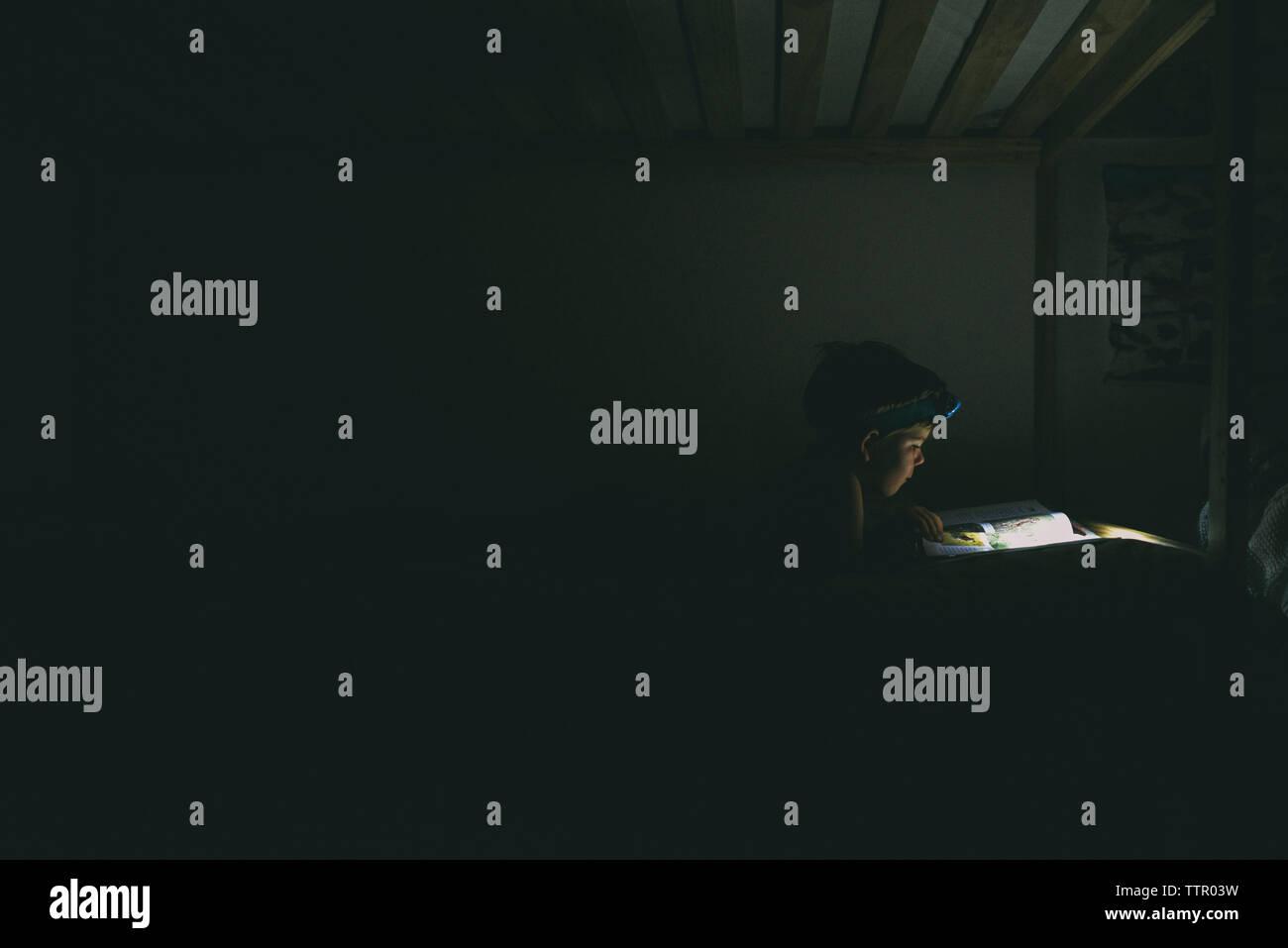 Boy using headlamp while reading book in darkroom - Stock Image