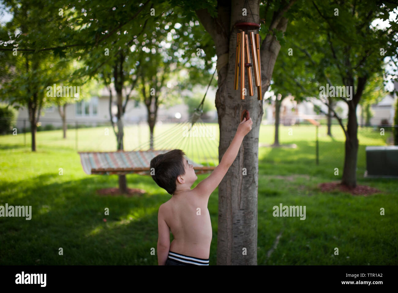 Shirtless boy playing with wind chime while standing at backyard - Stock Image