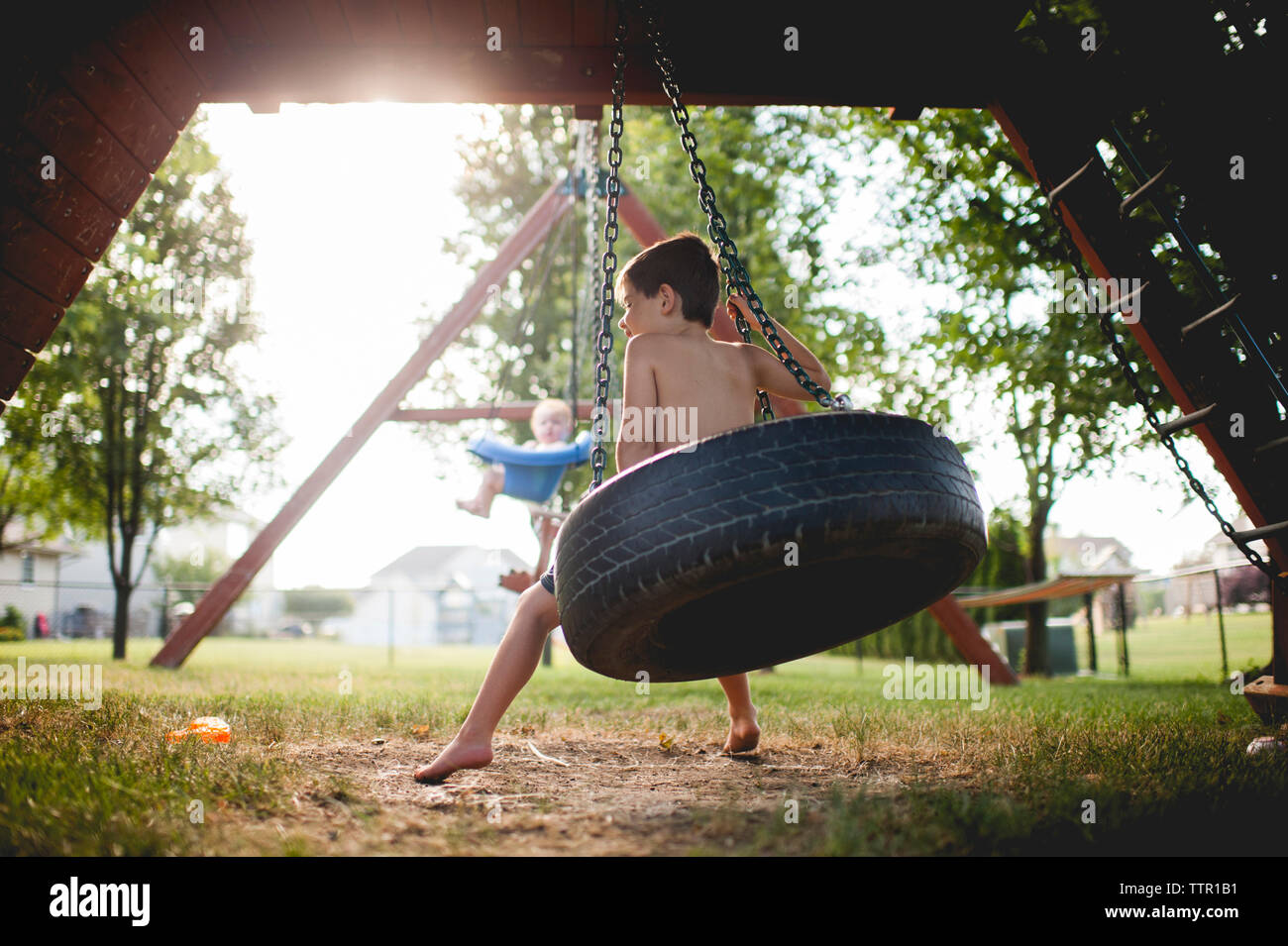 Brothers swinging at playground - Stock Image